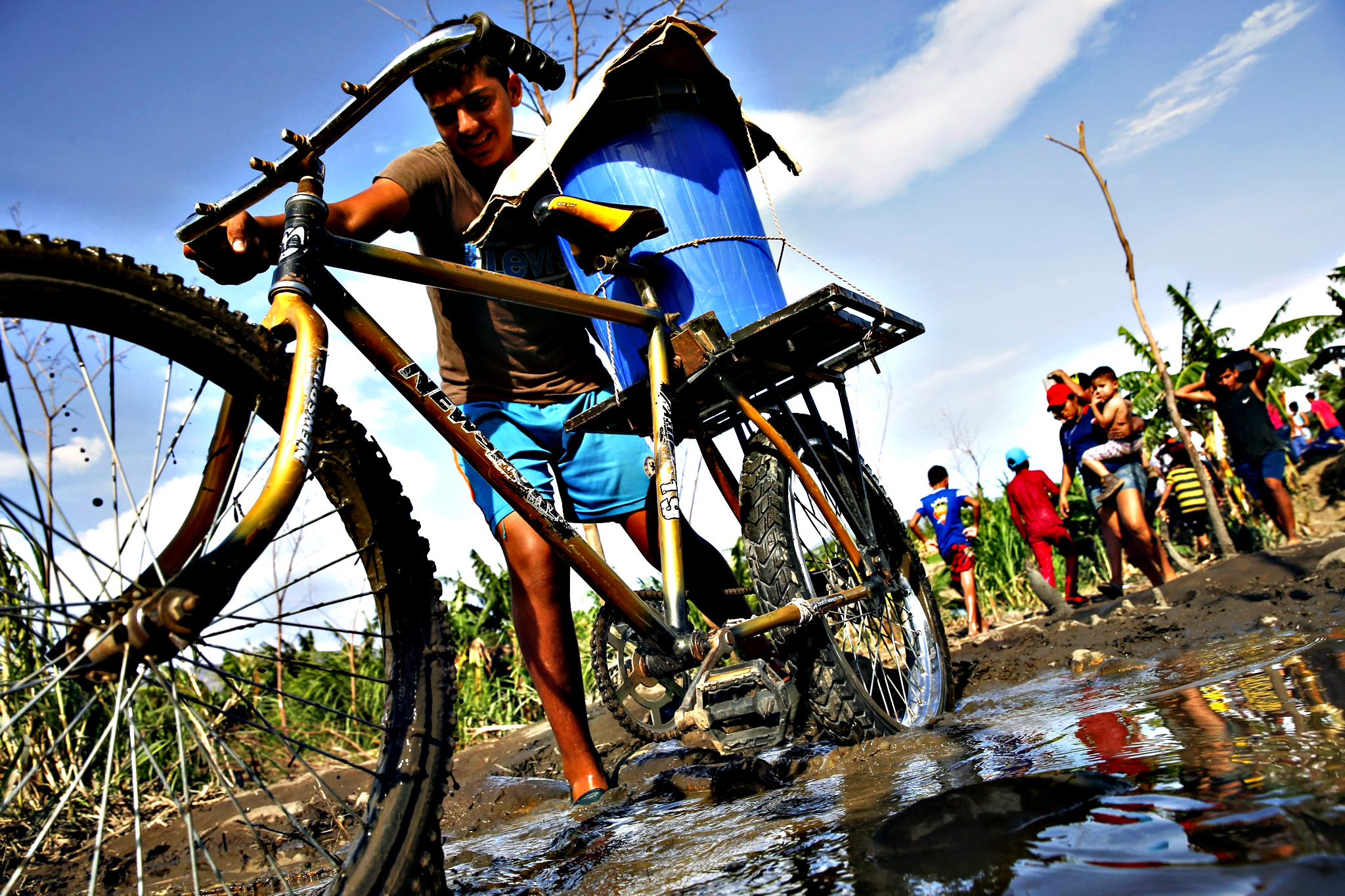 A boy pushes his bicycle loaded with a bucket across a dirt track next to people carrying their belongings, across to Colombia through the Tachira river at San Antonio in Tachira state, Venezuela...A boy pushes his bicycle loaded with a bucket across a dirt track next to people carrying their belongings, across to Colombia through the Tachira river at San Antonio in Tachira state, Venezuela