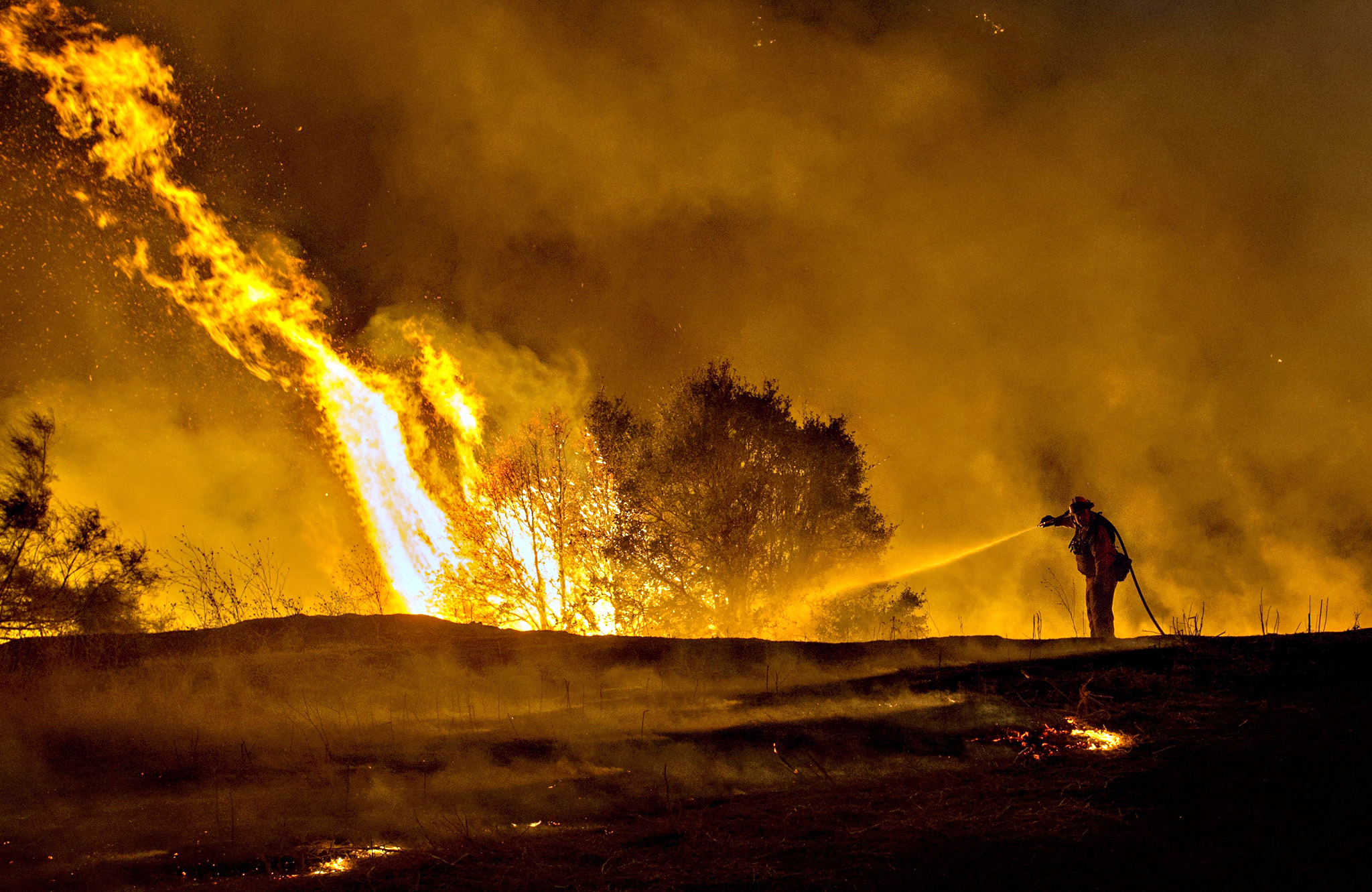 Firefighter Joe Darr douses flames of the Rocky fire along Highway 20 near Clearlake, California. Thousands of firefighters battled raging wildfires on August 2 in drought-parched California, where officials evacuated entire neighborhoods and closed miles of highway in the path of the inferno, which has claimed at least one life.