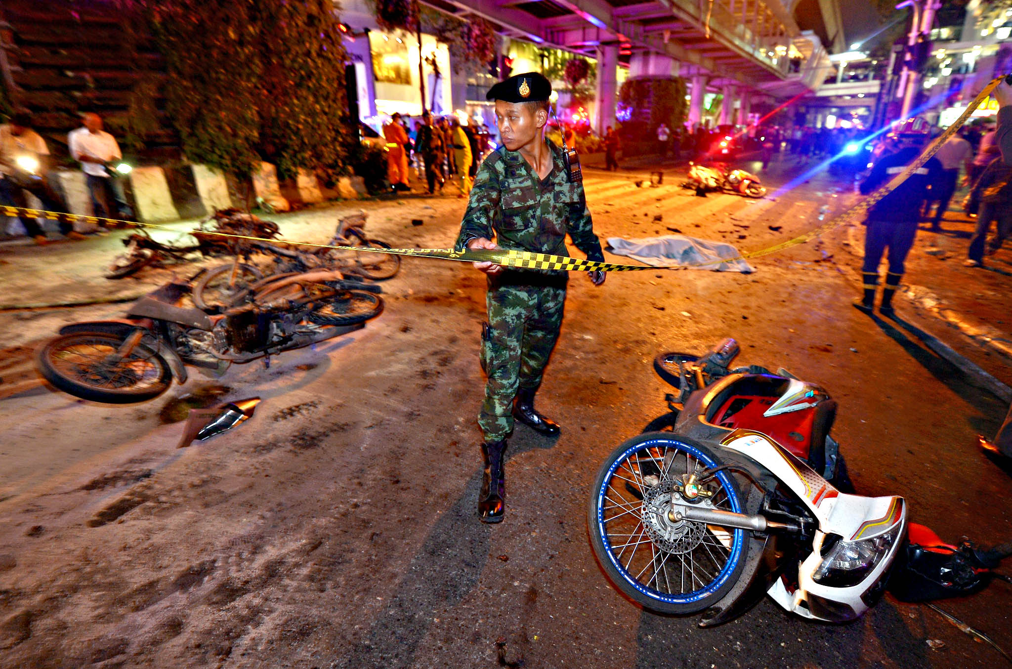 A Thai soldier ropes off the scene after a bomb exploded outside a religious shrine in central Bangkok late on August 17, 2015 killing at least 10 people and wounding scores more.  Body parts were scattered across the street after the explosion outside the Erawan Shrine in the downtown Chidlom district of the Thai capital