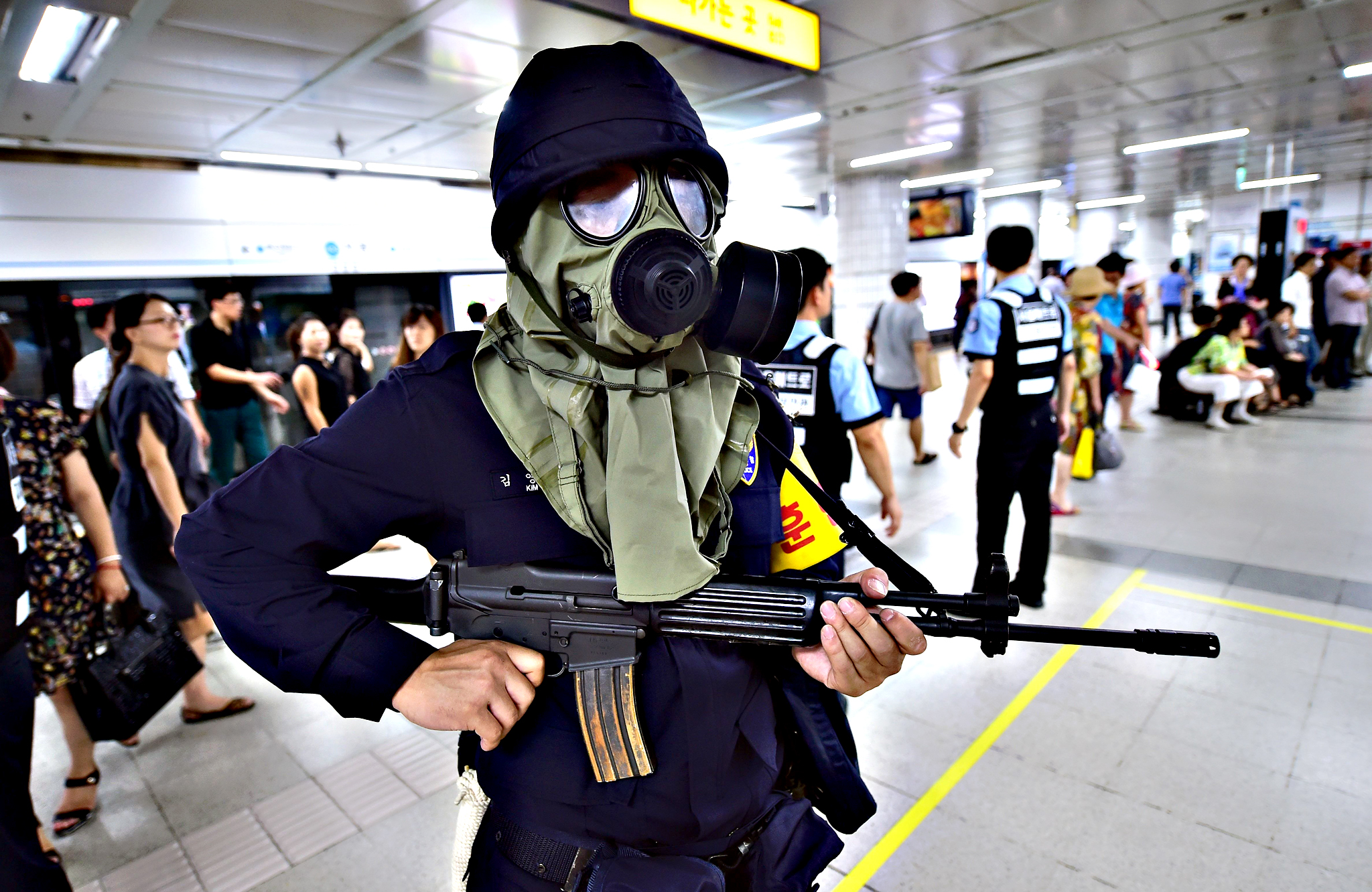 A South Korean armed policeman wears a gas mask during an anti-terror drill on the sidelines of South Korea-US joint military exercise, called Ulchi Freedom Guardian, at a subway station in Seoul on August 19, 2015. Tens of thousands of South Korean and US troops on August 17 began a military exercise simulating an all-out North Korean attack, as Pyongyang matched Seoul in resuming a loudspeaker propaganda campaign across their heavily-fortified border