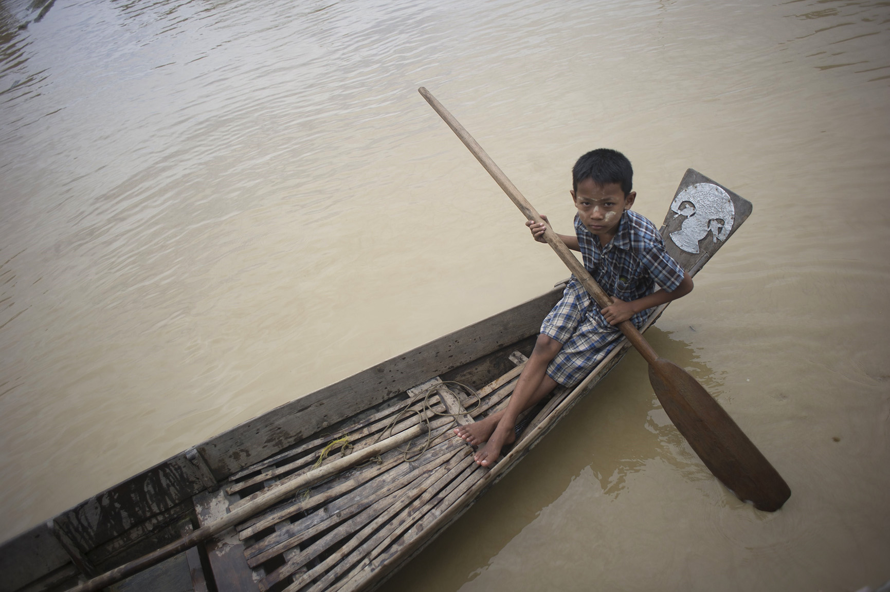 A flood-affected resident rides on a small boat in floodwaters at the Kyauk Ye village