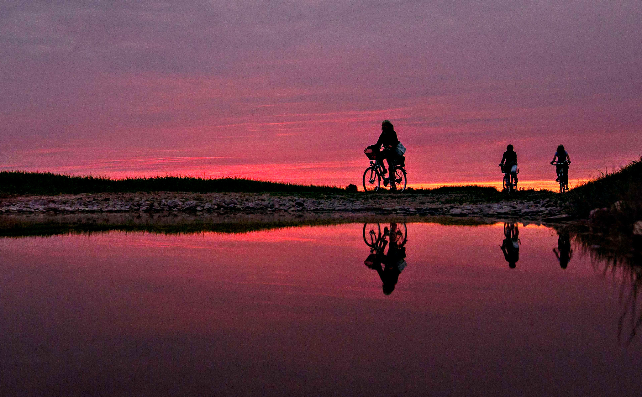 Cyclists reflect in a puddle and silhouette against the sky as sun sets near Guelpe, northeastern Germany