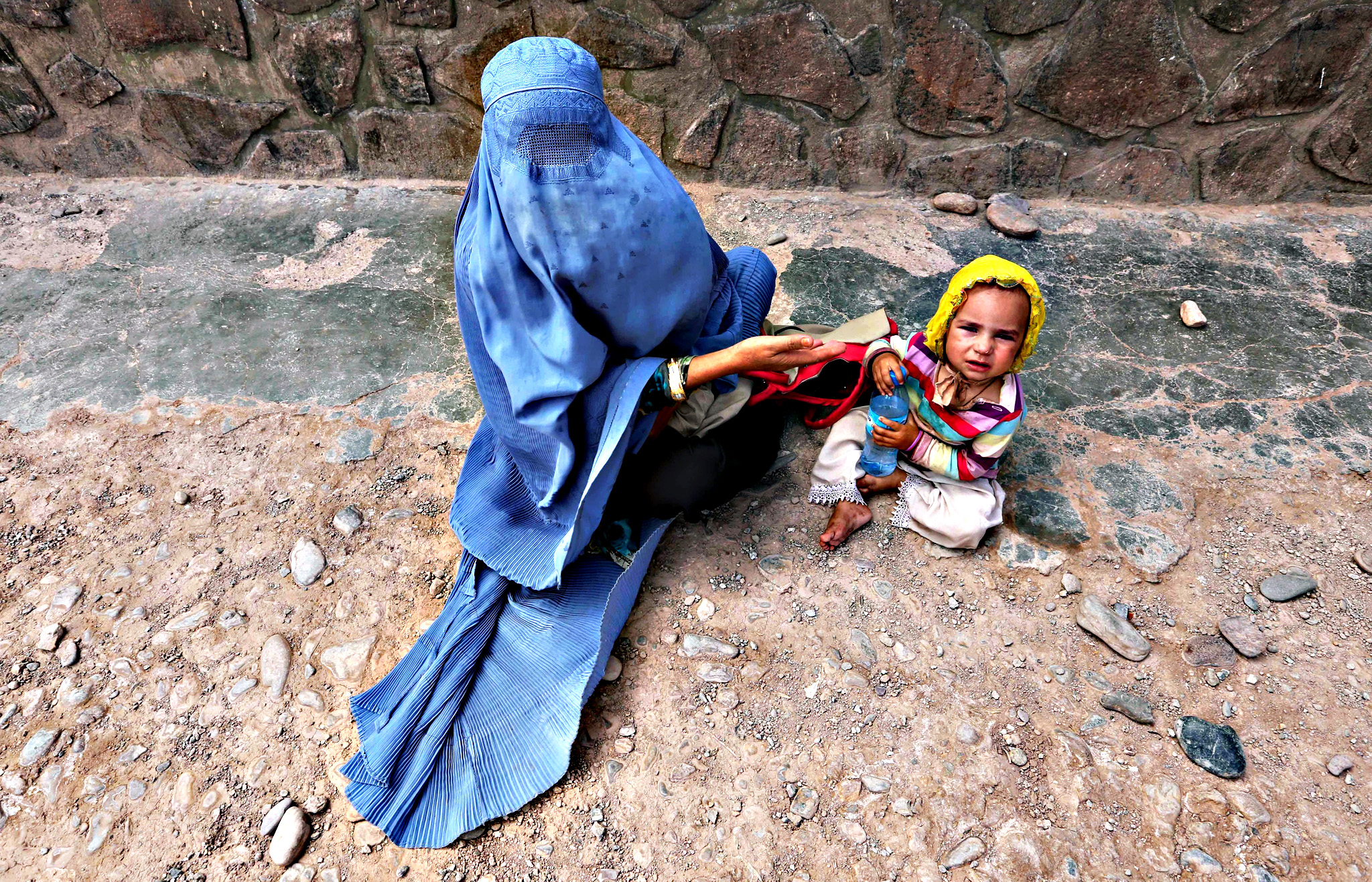 An Afghan woman waits to get medical treatment at the refugee camp in Herat, Afghanistan on Monday. The camp provides refugees with basic medical treatment, education, food and hygiene