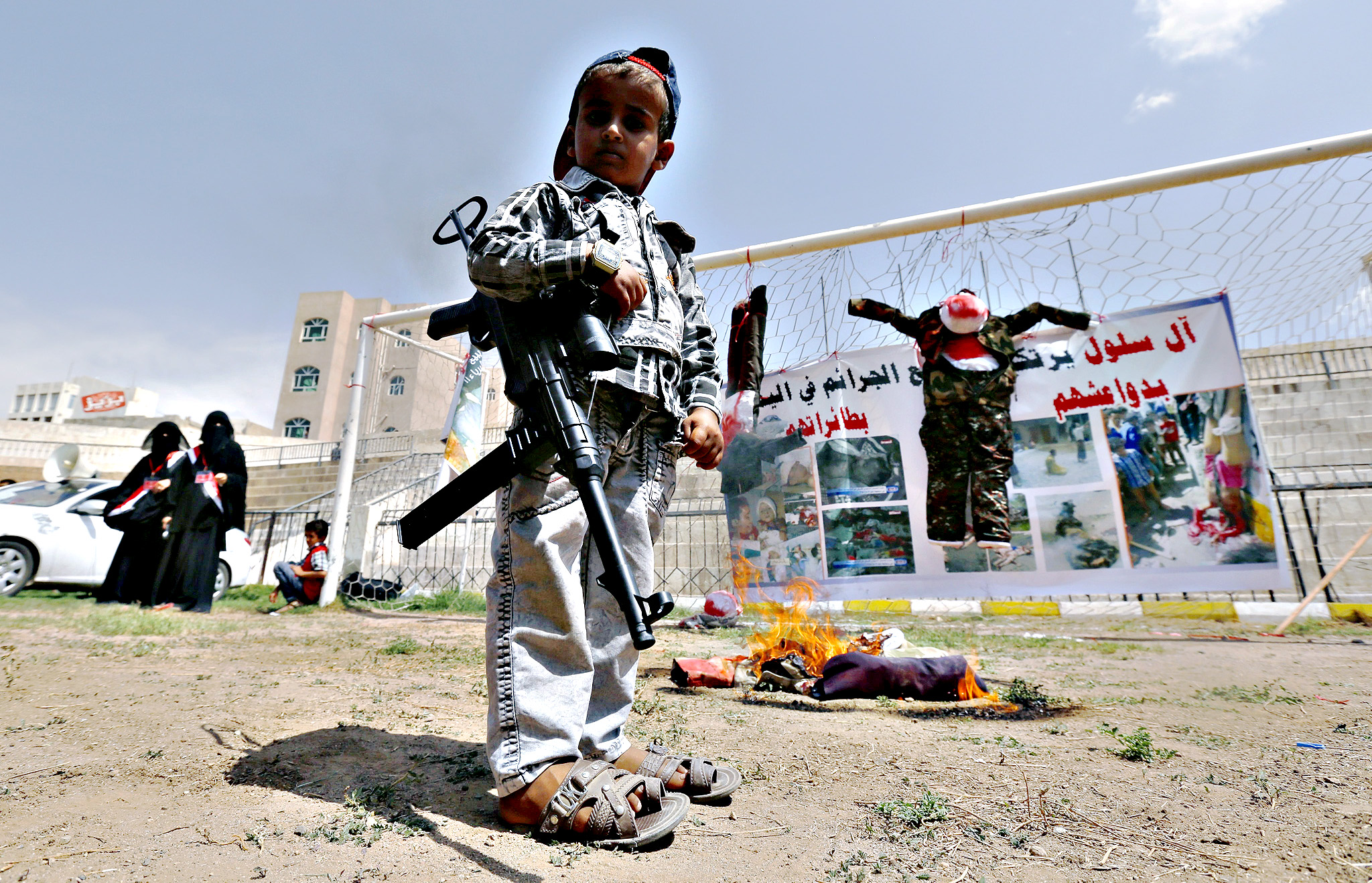 A young Yemeni holds an automatic weapon stands near effigies depicting the victims of the ongoing conflict during a rally against the military offensive carried out by the Saudi-led coalition, in Sanaa, Yemen