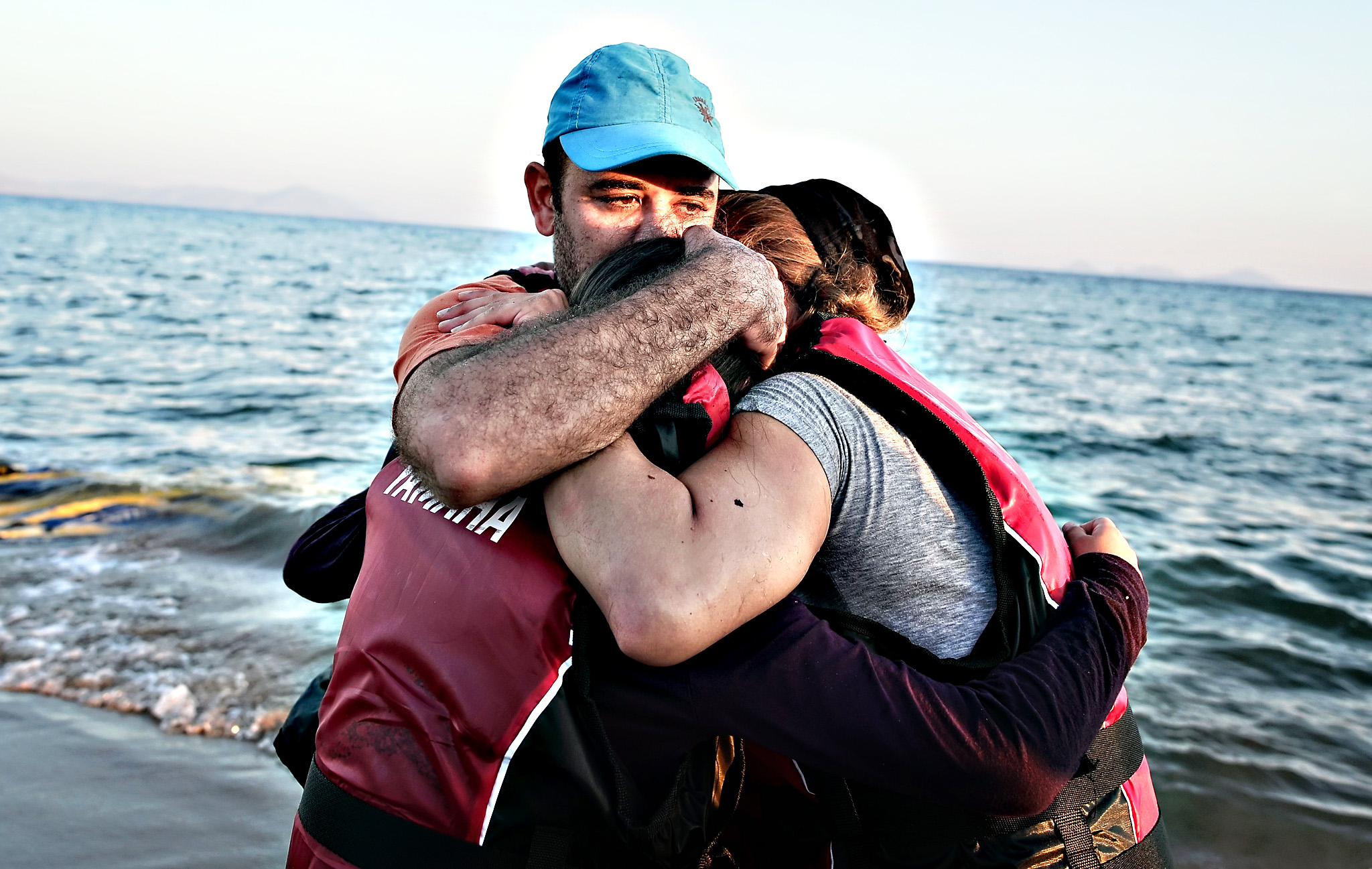A migrant hugs his family after safetly arriving to the shores of Kos island from Turkey on Tuesday. Authorities on the island of Kos have been so overwhelmed that the government sent a ferry to serve as a temporary centre to issue travel documents to Syrian refugees -- among some 7,000 migrants stranded on the island of about 30,000 people. The early hours are the safest time for migrants travelling from Turkey to the Greek islands just across the water, which have seen a huge influx of refugees escaping the civil war in Syria and chaos in Afghanistan since the beginning of this year.