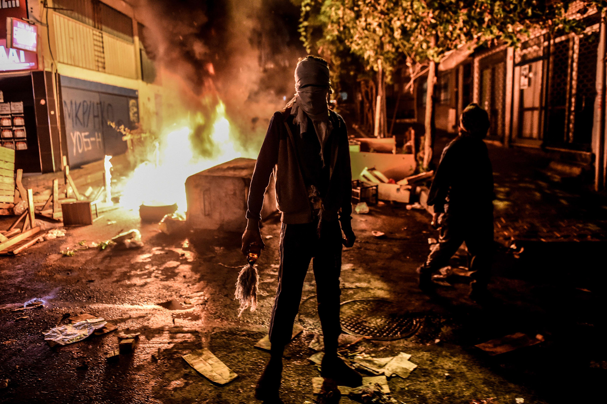 masked kurdish militant holds a molotov cocktails in front of a burning barricade during clashes with Turkish police