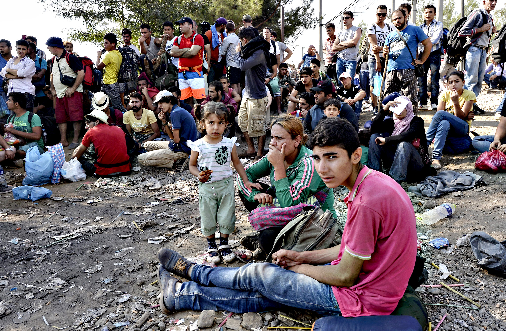 Migrants wait on the Greek side of the border to pass into Macedonia near southern city of Gevgelija, The Former Yugoslav Republic of Macedonia, 20 August 2015. Macedonian special police forces arrived this morning and blocked the illegal border crossing between Macedonia and Greece. They don't give permission to the migrants to pass in Macedonia. Number of migrants who passing through Macedonia increase day by day. From the beginning of the year to mid-June 2015, nearly 160,000 migrants landed in the southern European countries, mainly Greece and Italy, on their way to wealthier countries in Western and Northern Europe, according to estimates by the International Organization for Migration (IOM