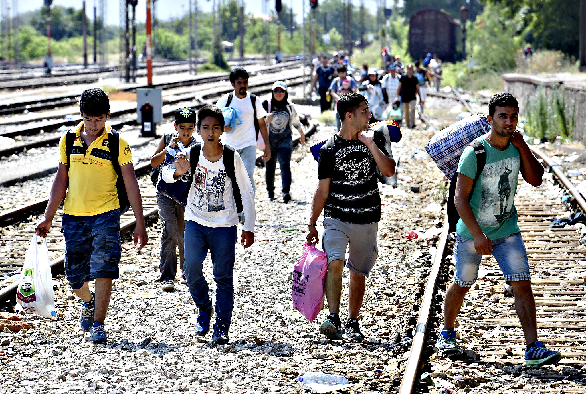 Migrants walk along railway tracks on their way to catch a train heading to the Serbian border, at the train station in Gevgelija, The Former Yugoslav Republic of Macedonia, 04 August 2015. Greece and Italy are the main entry points for Europe-bound asylum seekers and economic migrants. After they have reached the bloc, many start to make their way to wealthier countries in Western Europe. From the beginning of the year to mid-June, nearly 160,000 landed in both countries, according to International Organization for Migration (IOM) estimates