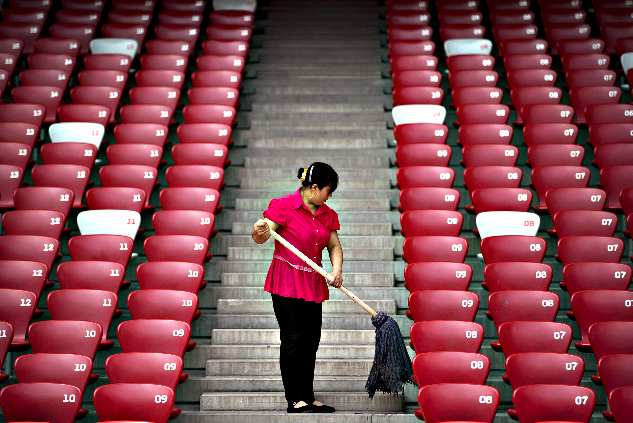 A maintenance worker mops steps at the Beijing Olympic Stadium, also known as the Bird's Nest, in Beijing, Thursday, Aug. 20, 2015. Final preparations are being World Athletics Championships, which runs from Aug. 22 to 30.