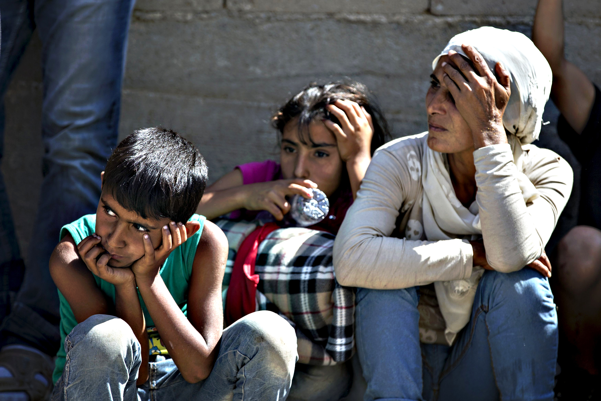Migrants from Syria sit along a road as they wait for a bus in the village of Miratovac near the town of Presevo, Serbia August 24, 2015. Long lines of migrants, many of them refugees from Syria, snaked through southern Serbia by foot on Monday before jumping on trains and buses north to Hungary and the last leg of an increasingly desperate journey to western Europe