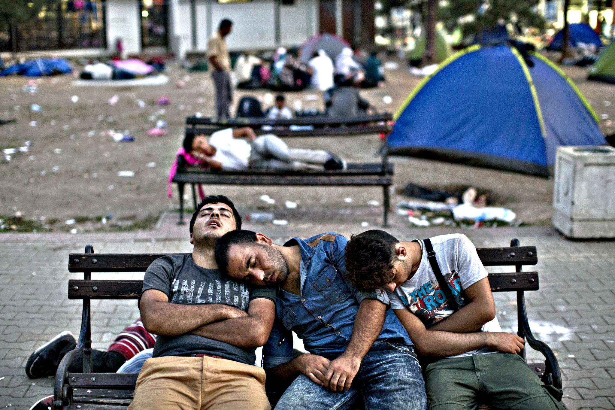 Migrants sleep on a bench at a park in Belgrade, Serbia, Friday, Aug. 28, 2015. Over 10,000 migrants, including many women with babies and small children, have crossed into Serbia over the past few days and headed toward Hungary and the EU Schengen Area, a zone with no internal border checks between member countries