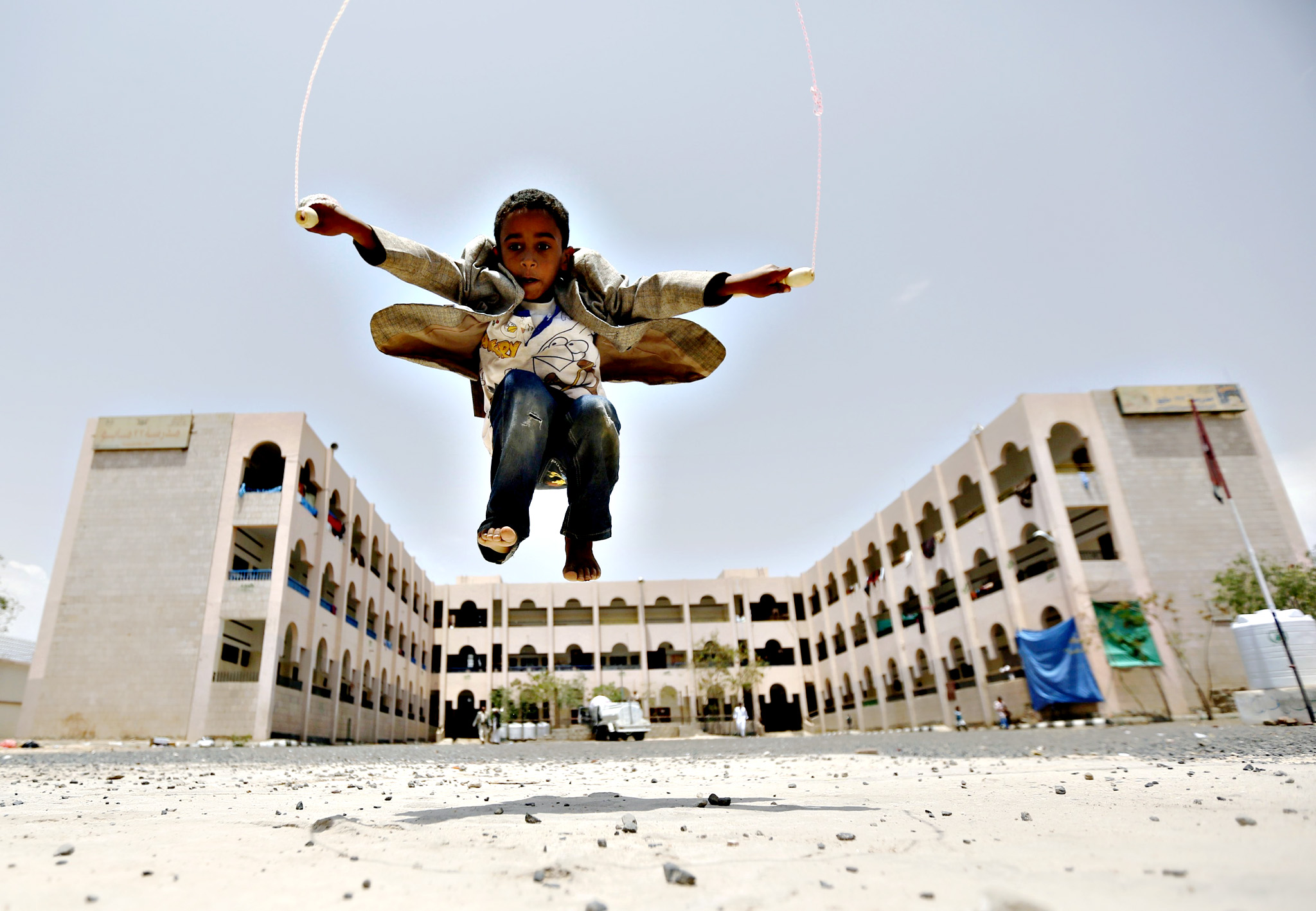 A boy skips at a school in Yemen's capital Sanaa sheltering people after the conflict forced them to flee their areas from the Houthi-controled northern province of Saada August 4, 2015. A Saudi-led Arab alliance launched a military campaign on March 26 to end Houthi control over much of Yemen and to return President Abd-Rabbu Mansour Hadi from exile