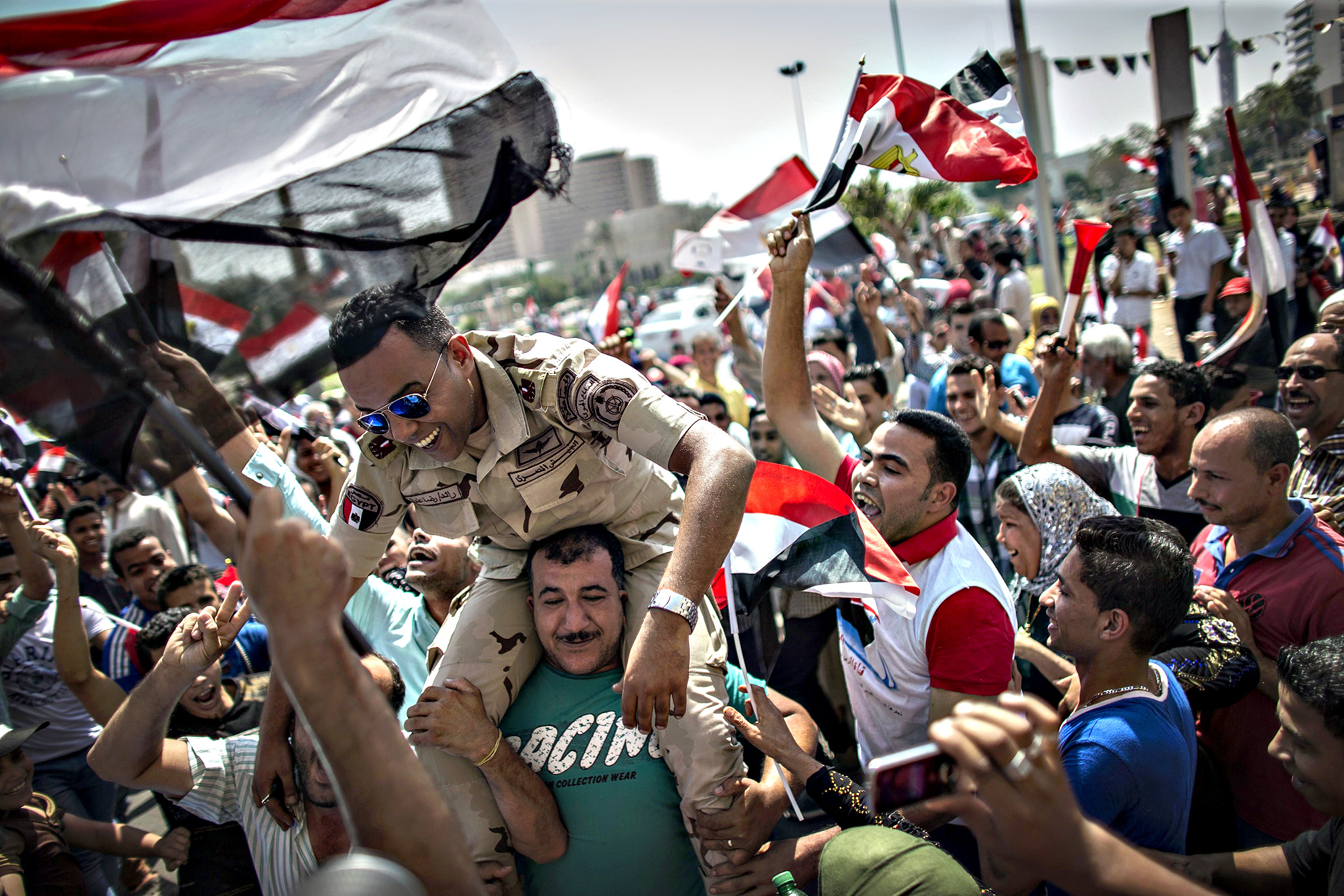 An Egyptian carries a member of the armed forces on his shoulders during celebrations of the opening of the new addition to the Suez Canal, in Tahrir Square, downtown Cairo, Egypt, 06 August 2015. The latest addition to the canal comes in at 72 kilometers (44 miles), was completed in under a year at an estimated cost of 8.5 billion US dollars, and was opened to shipping 06 August. According to the Egyptian Government the additional chanel cuts journey times from an estimated 18-14 hours to 11 hours, making it the fastest shipping lane of its kind worldwide, and will double revenue, though their figures have been widely disputed by international economists
