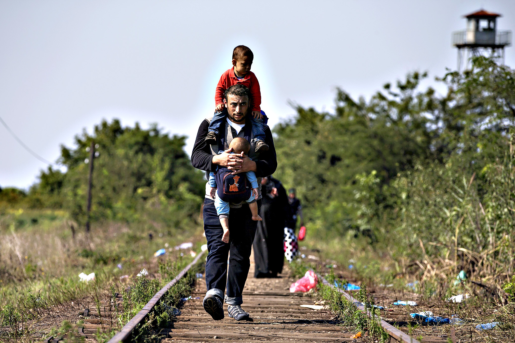 A Syrian migrant carries children as he walks along railway track to cross Serbian border with Hungary near the village of Horgos...A Syrian migrant carries his children as he walks along a railway track to cross the Serbian border with Hungary near the village of Horgos August 27, 2015. Hungary made plans on Wednesday to reinforce its southern border with helicopters, mounted police and dogs, and was also considering using the army as record numbers of migrants, many of them Syrian refugees, passed through coils of razor-wire into Europe