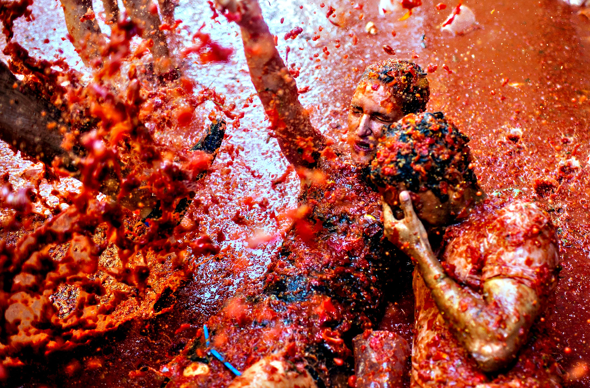 The World's Biggest Tomato Fight At Tomatina Festival...BUNOL, SPAIN - AUGUST 26:  Revellers enjoy the atmosphere in tomato pulp while participating the annual Tomatina festival on August 26, 2015 in Bunol, Spain. An estimated 22,000 people threw 150 tons of ripe tomatoes in the world's biggest tomato fight held annually in this Spanish Mediterranean town.