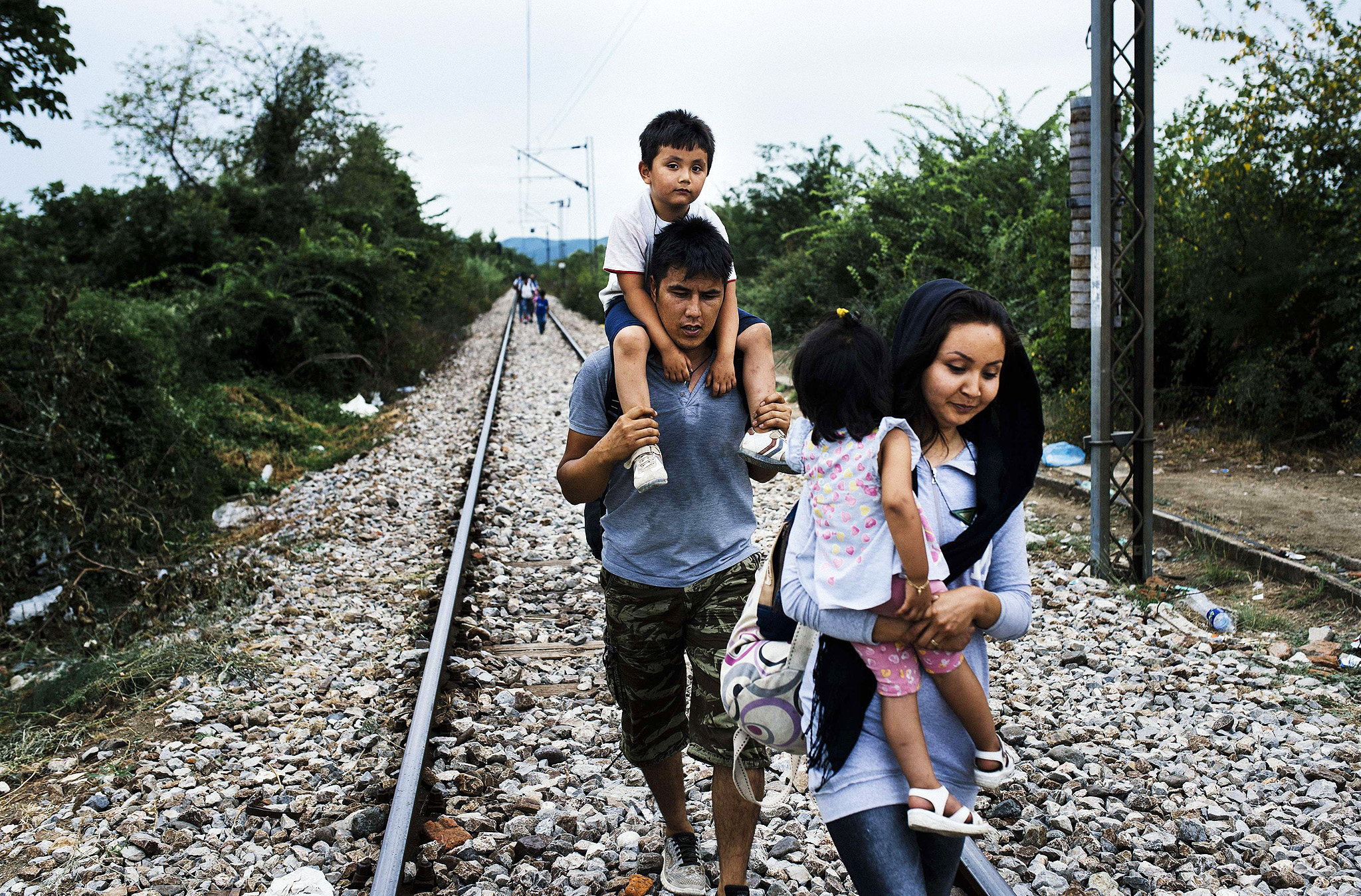 A migrant family walks on train tracks towards the town of Gevgelija, on the Macedonian-Greek border, on August 6, 2015. Many migrants try to cross Macedonia and Serbia to enter the European Union via Hungary, a country that will finish building its anti-migrant fence on its southern border with Serbia by August 31, ahead of a previous November deadline