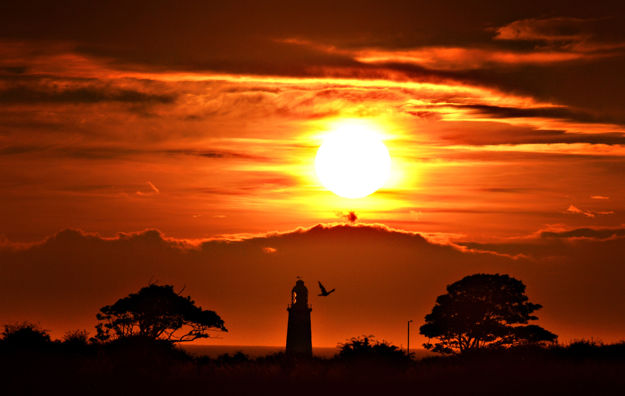 "The sun rises over Whitley Bay with the top of St Mary's lighthouse visible, as hot and humid air is expected to be pushed into northern Europe this weekend, including Britain, creating a ""Spanish Plume"""