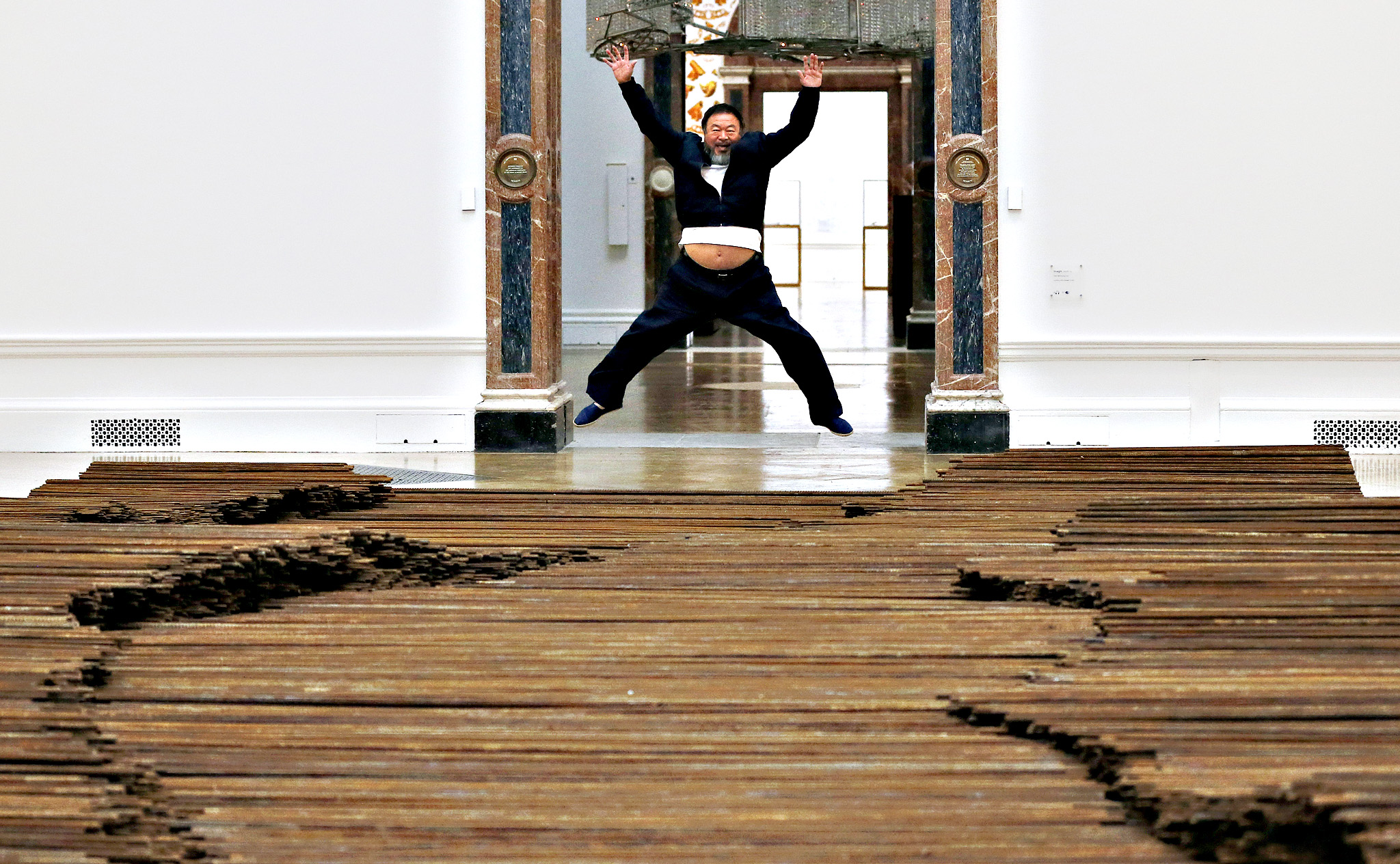 Chinese artist Ai Weiwei poses for photographers with one of his pieces at his exhibition at the Royal Academy of Arts in London, Tuesday, Sept. 15, 2015. The exhibition opens to the public on September 19th