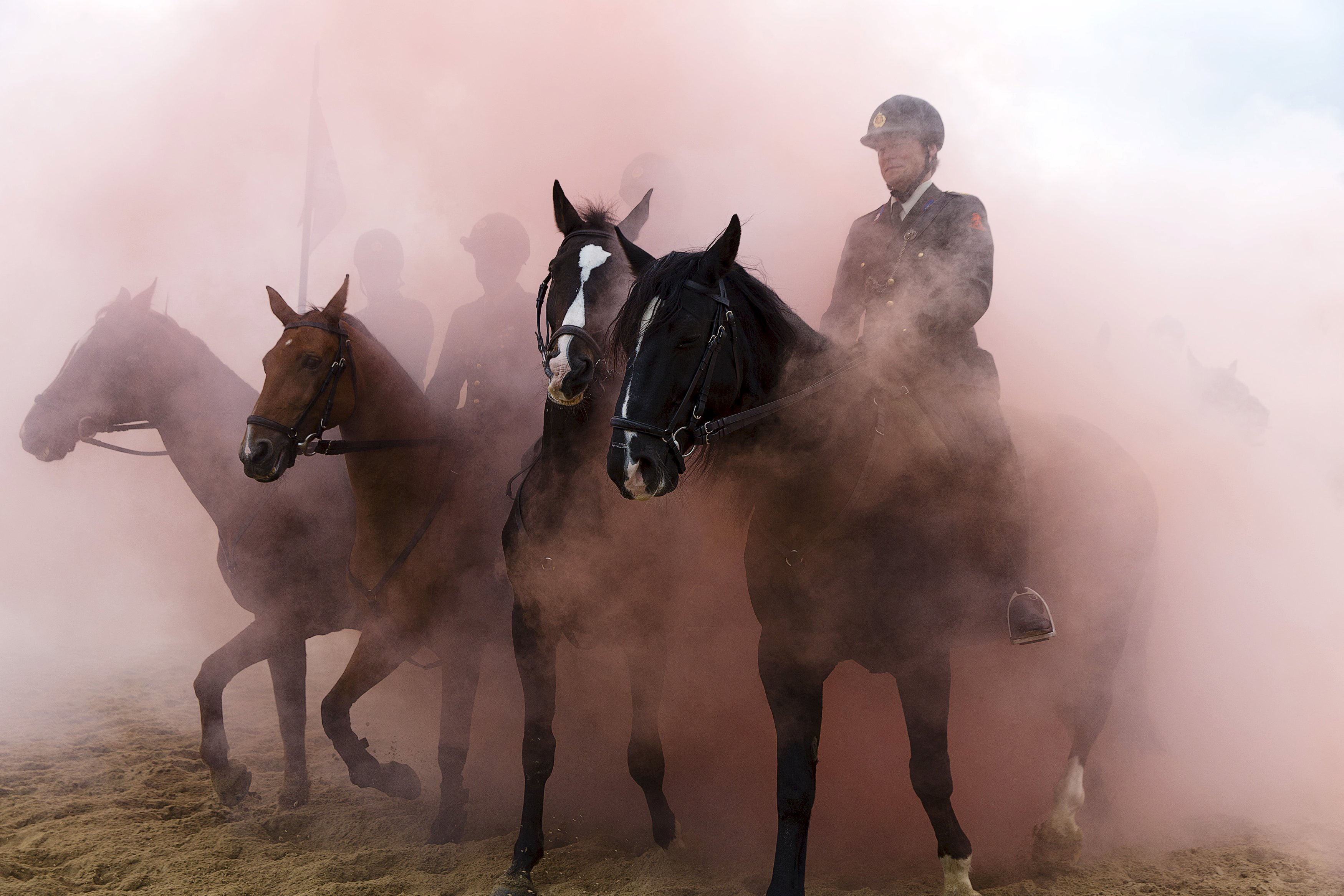 Members of the Dutch Royal Guard guide their horses through clouds of thick smoke and gunfire on the beach of Scheveningen, near The Hague to prepare for the presentation of the Dutch 2016 Budget Memorandum