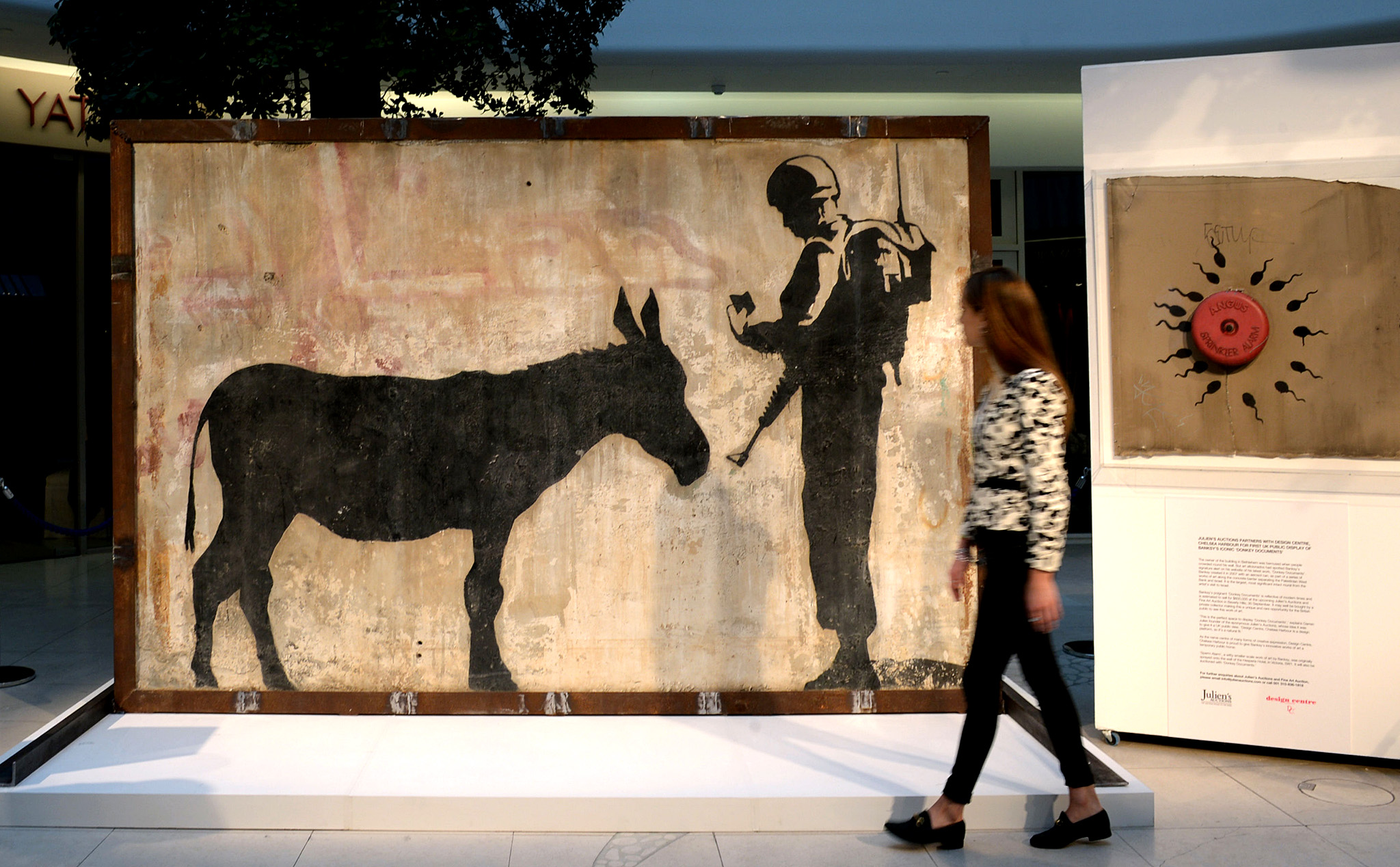 A woman views Banksy's 'Donkey Documents', an intact four ton mural from Jerusalem, in the Design Centre in Chelsea, London. PRESS ASSOCIATION Photo. Picture date: Monday September 21, 2015. Banksy created the work in 2007, as part of a series along the concrete barrier separating the Palestinian West Bank and Israel. The mural is estimated to sell for $600,000 at the forthcoming Julien's Fine Art Auction in Beverly Hills on 30 September. Photo credit should read: Anthony Devlin/PA Wire