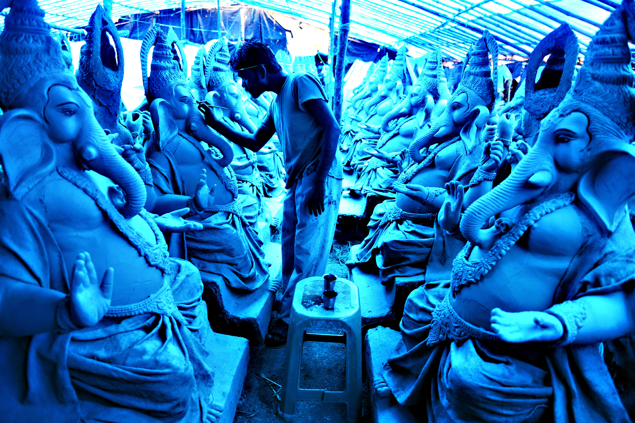 An Indian artist works on eco-friendly figures of Hindu God Lord Ganesh made with mud, jute and bamboo at a blue tarp-covered workshop on the outskirts of Hyderabad on Tuesday.  The statues of eco-friendly clay Ganesh idols made with mud, jute and bamboo will reduce pollution during the Ganesh immersion