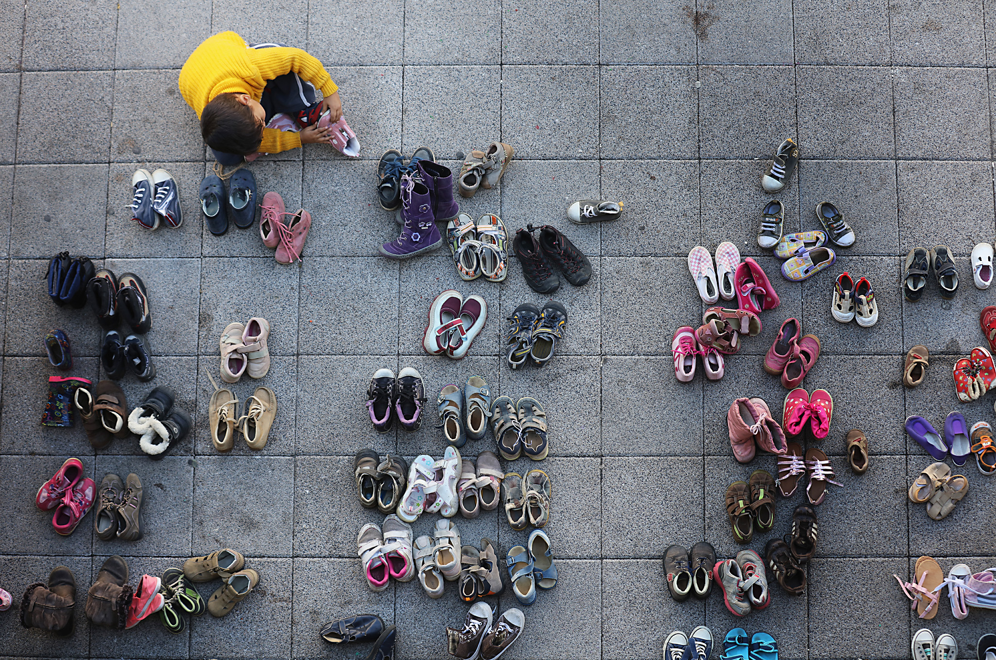 Migrants Continue To Arrive In Hungary...BUDAPEST, HUNGARY - SEPTEMBER 07:  A young migrant boy tries on shoes donated by the people of Hungary at Keleti station in Budapest on September 7, 2015 in Budapest, Hungary. After days of confrontation and chaos, Hungary unexpectedly opened its borders with Austria, allowing thousands of migrants to leave the country and travel onto Germany. (Photo by Christopher Furlong/Getty Images)