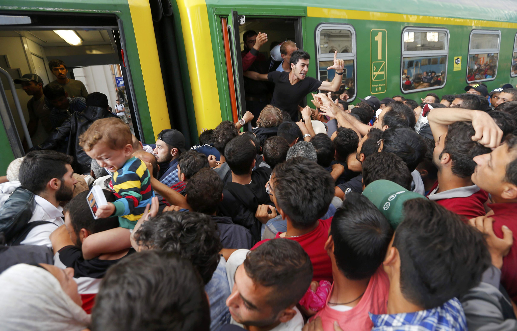 Migrants storm into a train at the Keleti train station in Budapest...Migrants storm into a train at the Keleti train station in Budapest, Hungary, September 3, 2015 as Hungarian police withdrew from the gates after two days of blocking their entry.      REUTERS/Laszlo Balogh
