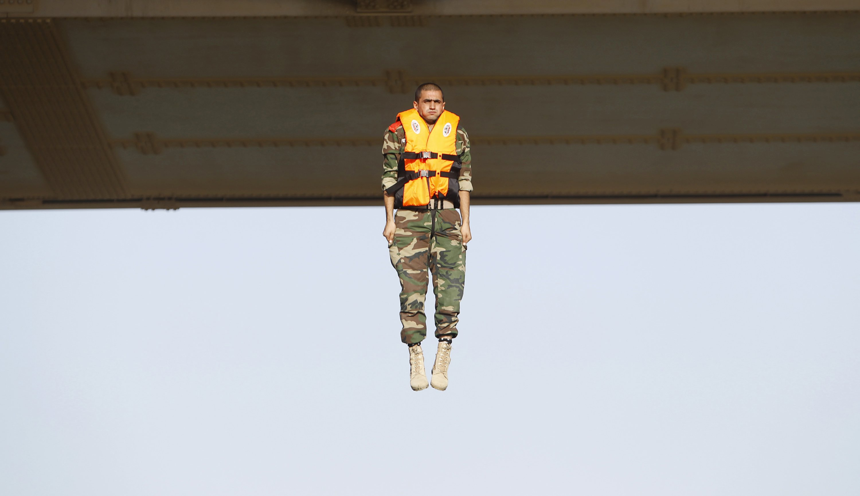 "An Iraqi army cadet performs ""the leap of faith"" from a bridge in Baghdad, September 22, 2015."