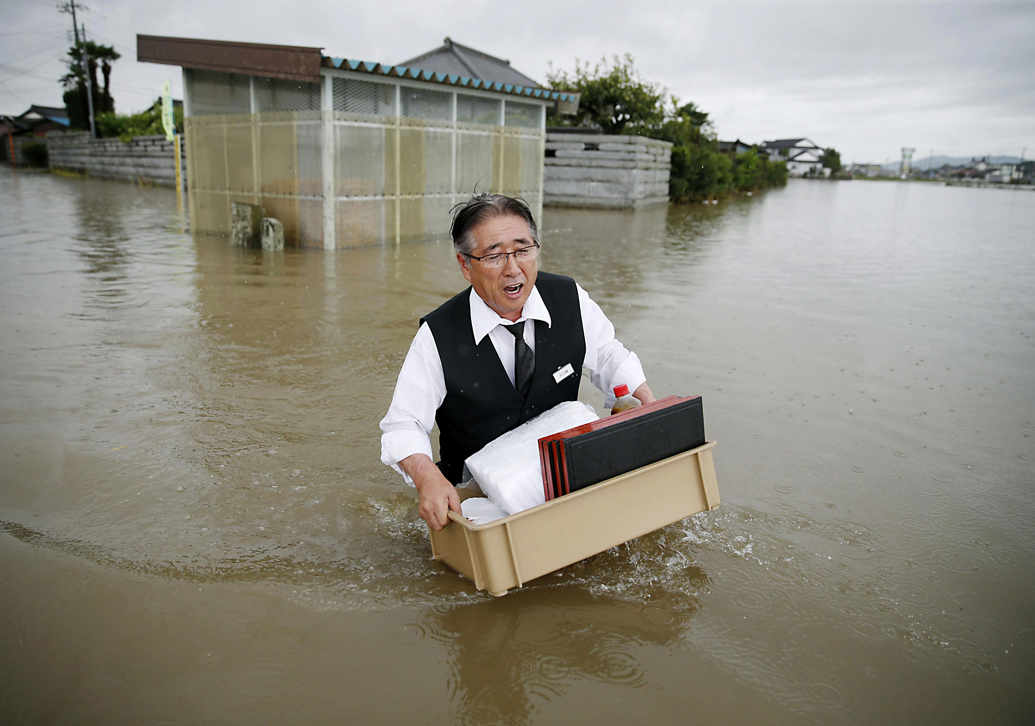 A man carries belonging through a flooded street in Oyama, Tochigi prefecture, northeast of Tokyo Thursday, Sept. 10, 2015. Heavy rain is pummeling Japan for a second straight day, overflowing rivers and causing landslides and localized flooding in the eastern part of the country. (Kyodo News via AP) JAPAN OUT, MANDATORY CREDIT