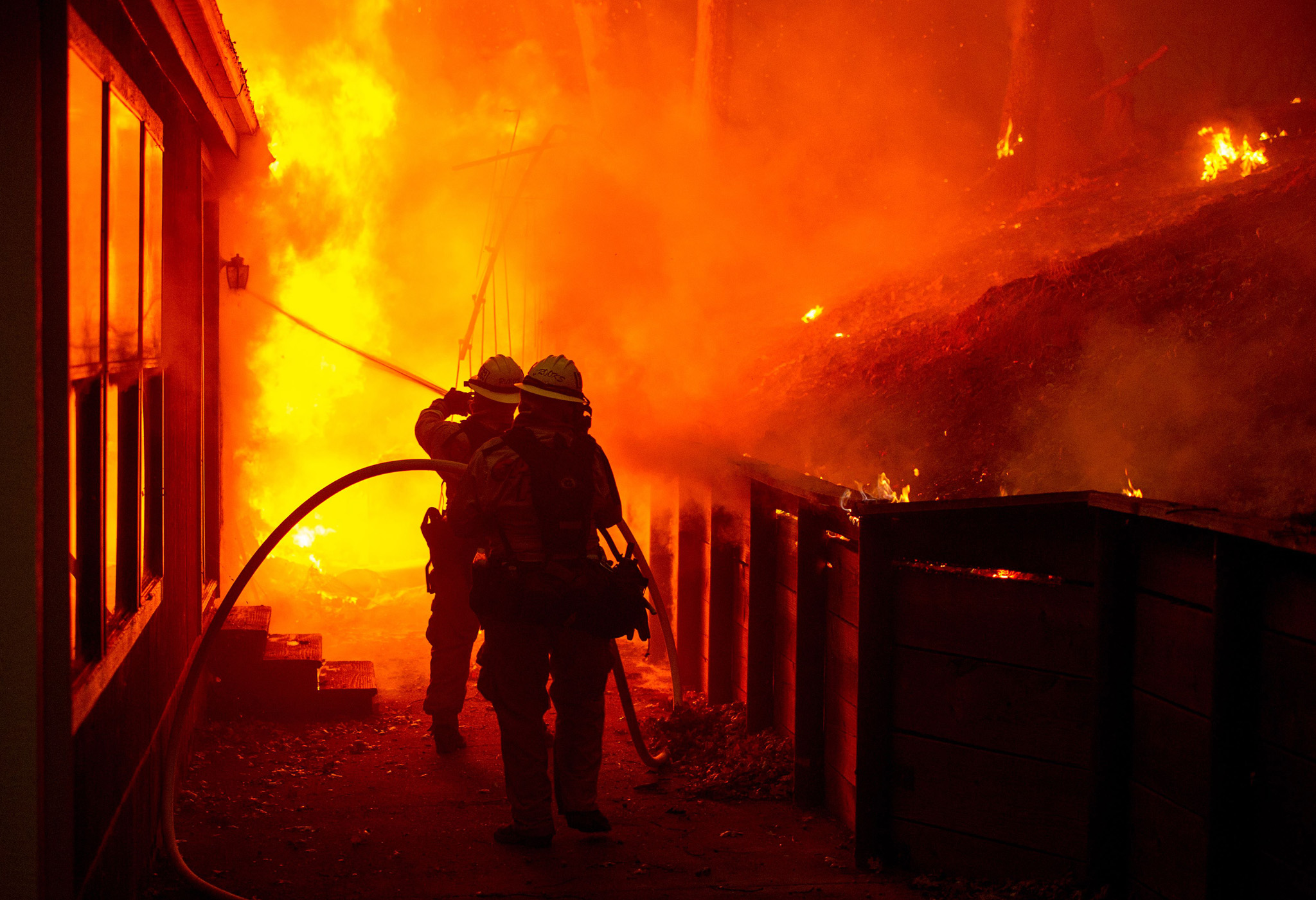 A house is engulfed in flames as firefighters attempt to put it out during the Valley fire in Seigler Springs, California.