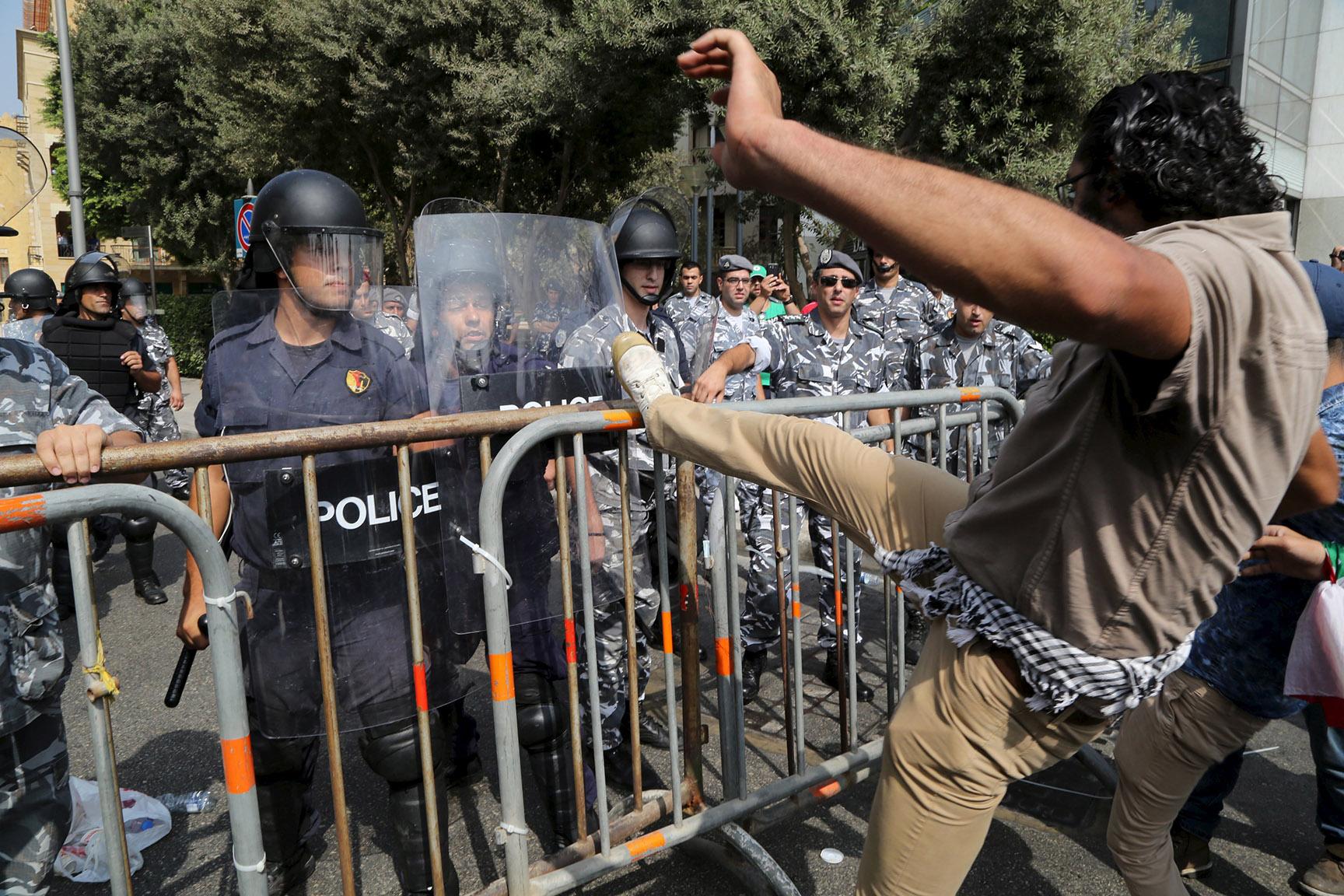 A protester kicks a barrier near riot police in downtown Beirut, Lebanon
