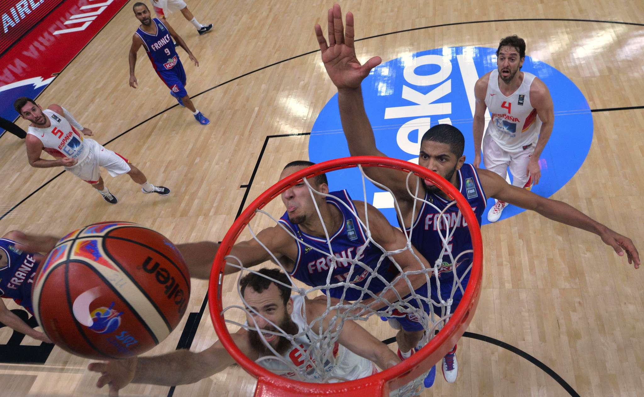 Spain's Sergio Rodriguez, bottom, dunks a basket while France's Rudy Gobert, center, and Nicolas Batum, right, try to block him during the EuroBasket European Basketball Championship semifinal match between France and Spain at Pierre Mauroy stadium in Lille, northern France.