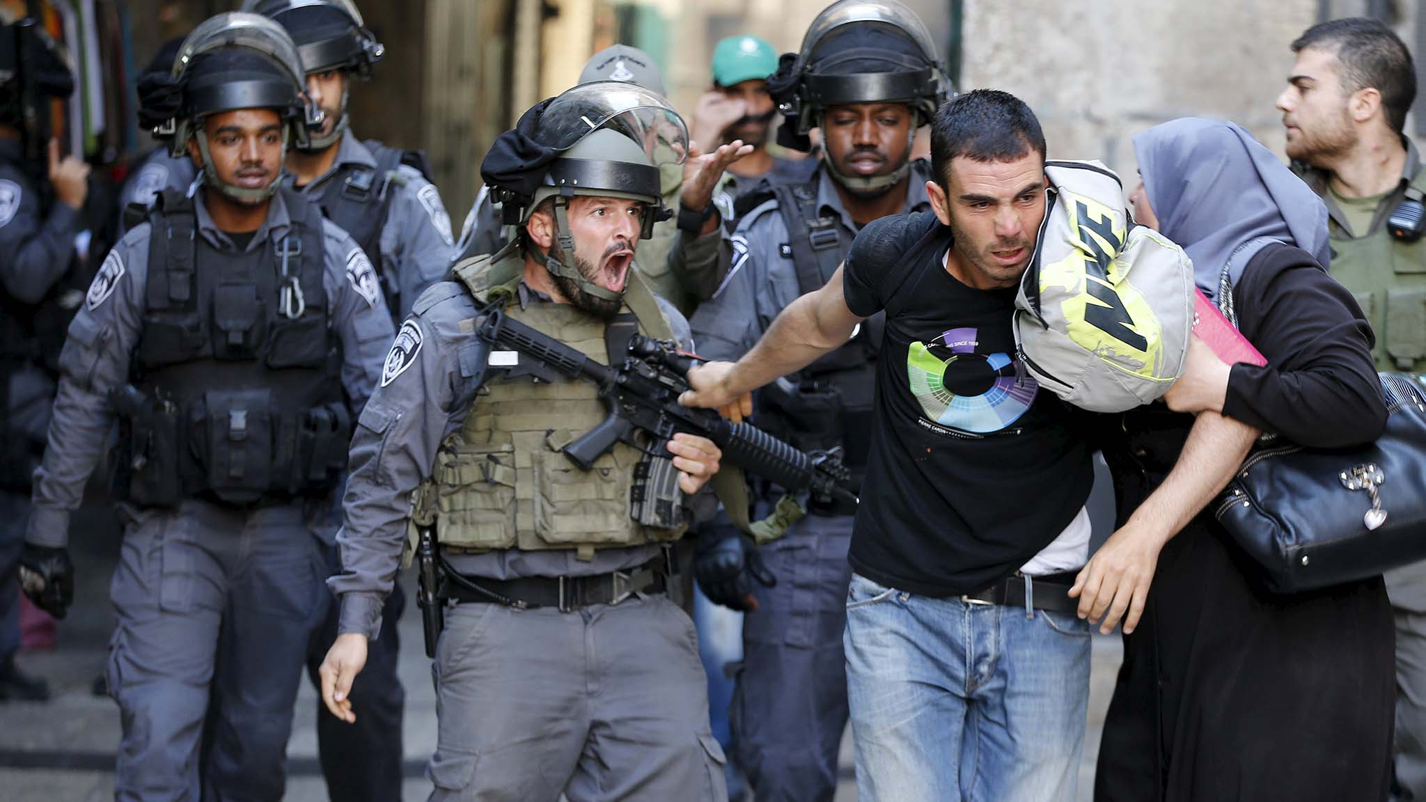 An Israeli policeman prevents a Palestinian man from entering  in Jerusalem's Old City
