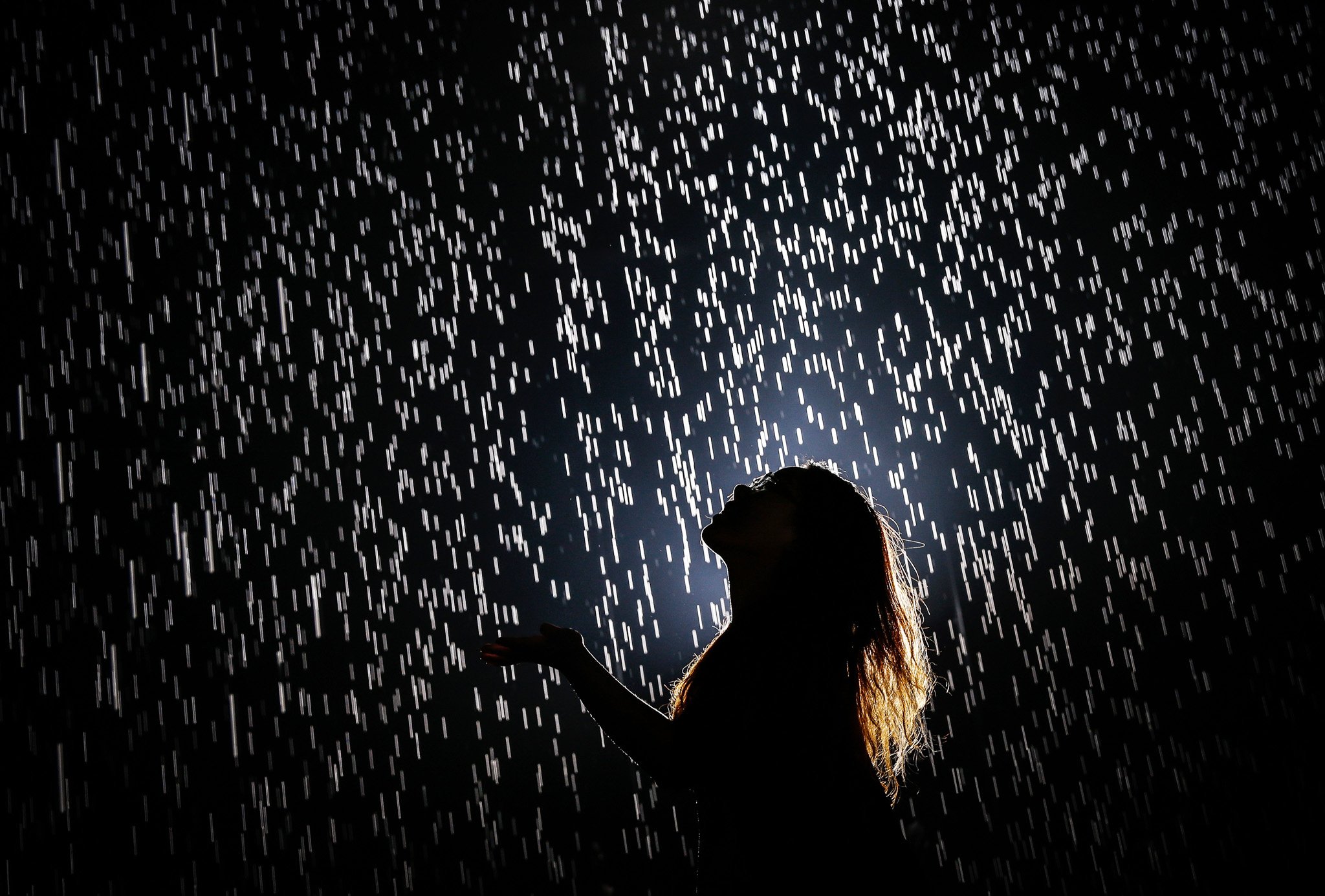 """""""Rain Room"""" Comes To Shanghai...SHANGHAI, CHINA - AUGUST 31: (CHINA OUT) A visitor walks through and experiences """"Rain Room"""" at Shanghai Yuz Museum on August 31, 2105 in Shanghai, China. Rain Room (2012), a large-scale environment by Random International, is presented at The Museum of Modern Art from May 12 to July 28, 2013, as part of EXPO 1: New York. Rain Room consists of a field of falling water that visitors may walk through and experience how it might feel to control the rain. The work also invites visitors to explore what role science, technology, and human ingenuity can play in stabilizing our environment. Using digital technology, Rain Room is a carefully choreographed downpour°™a monumental work that encourages people to become performers on an unexpected stage, while creating an intimate atmosphere of contemplation. It comes to China now and will be exhibited at Shanghai Yuz Museum from September 1 to December 31 for four months. (Photo by ChinaFotoPress/Getty Images)"""