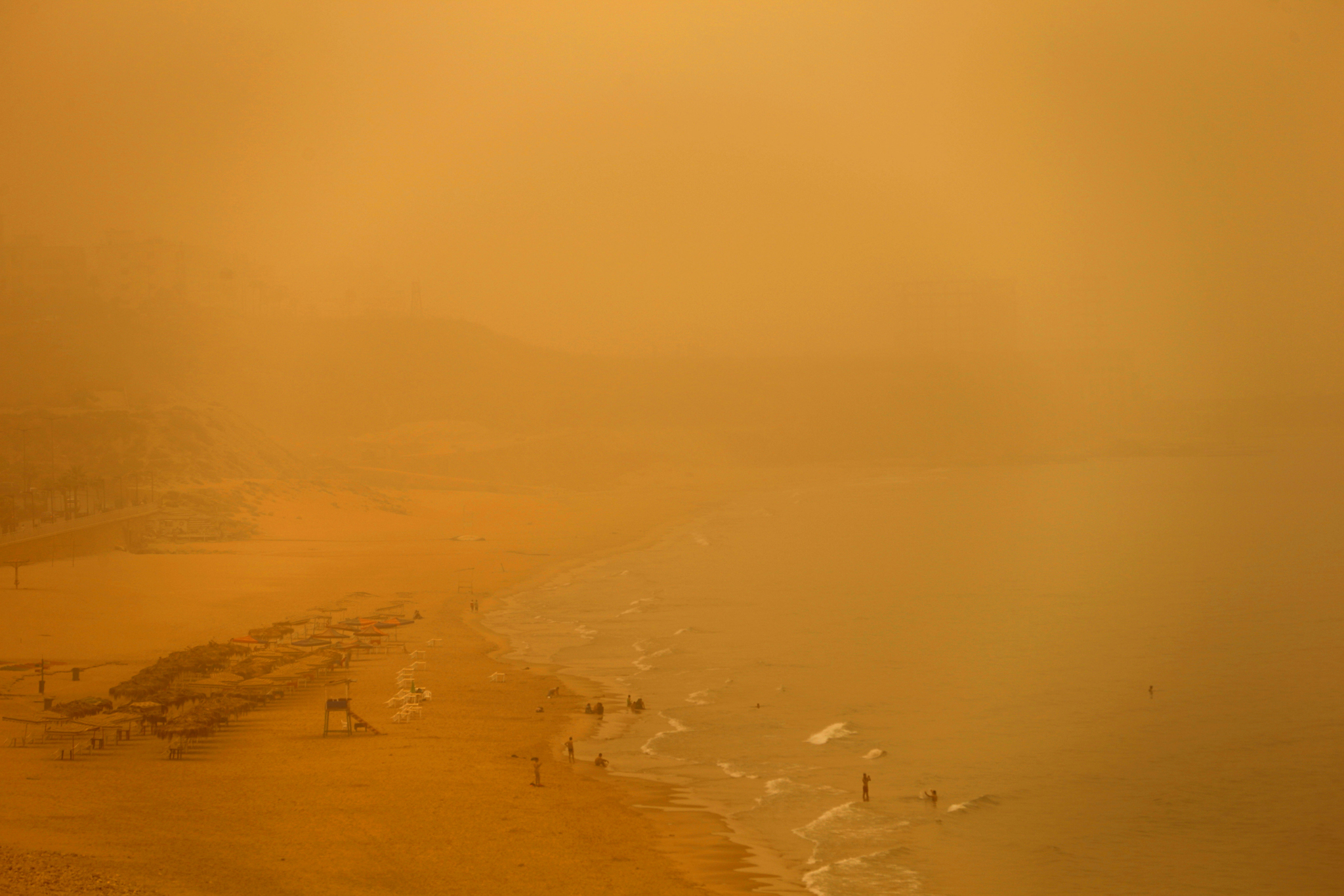 People swim at the public beach of Ramlet al Bayda during a sand  storm in Beirut, Lebanon, Tuesday, Sept. 8, 2015. An unseasonal  sandstorm has hit Lebanon and Syria, reducing visibility and sending  dozens to hospitals with breathing difficulties. (AP Photo/Hassan  Ammar)