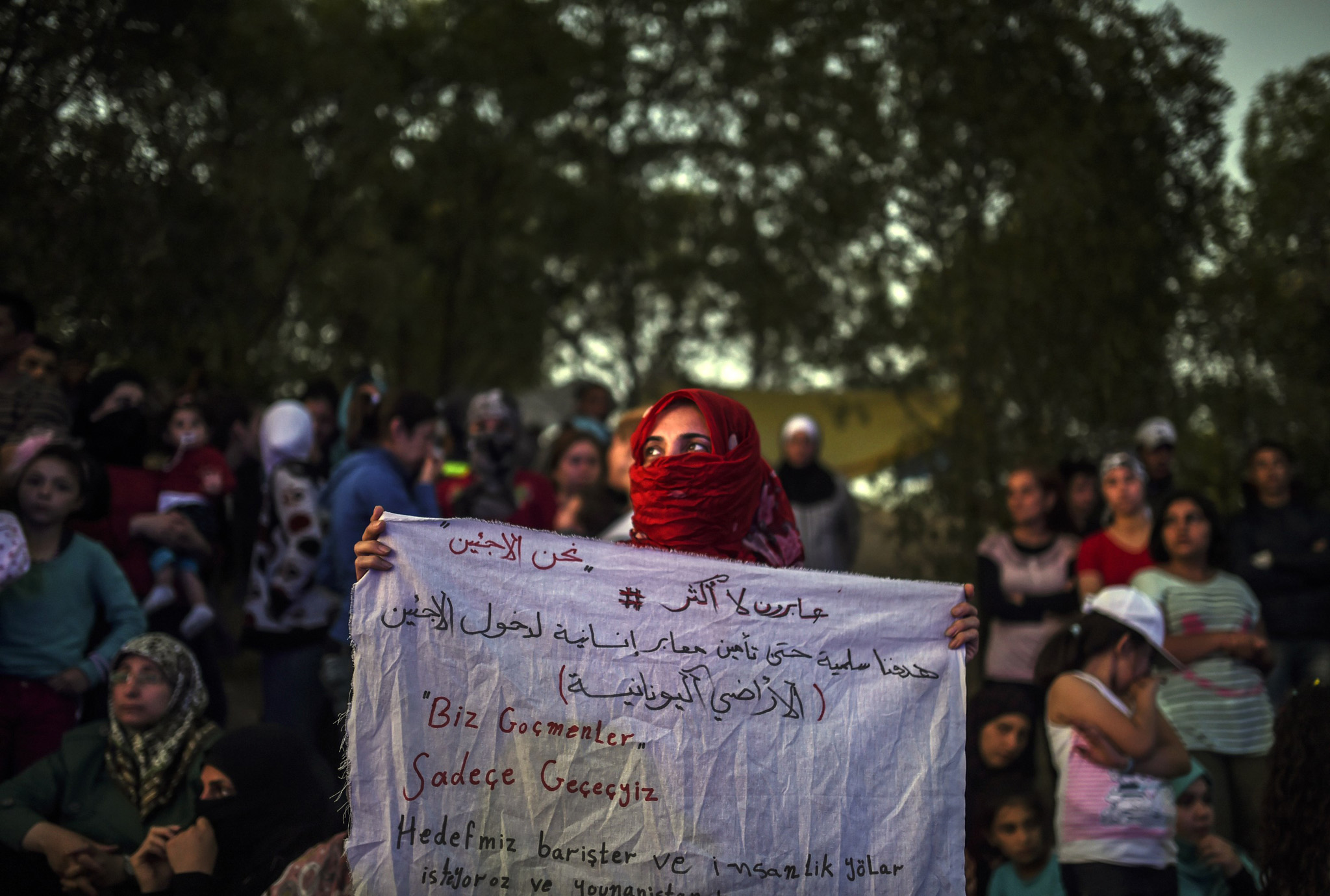A Syrian woman stands holding a banner that reads in Turkish ''we are migrants, we will pass''