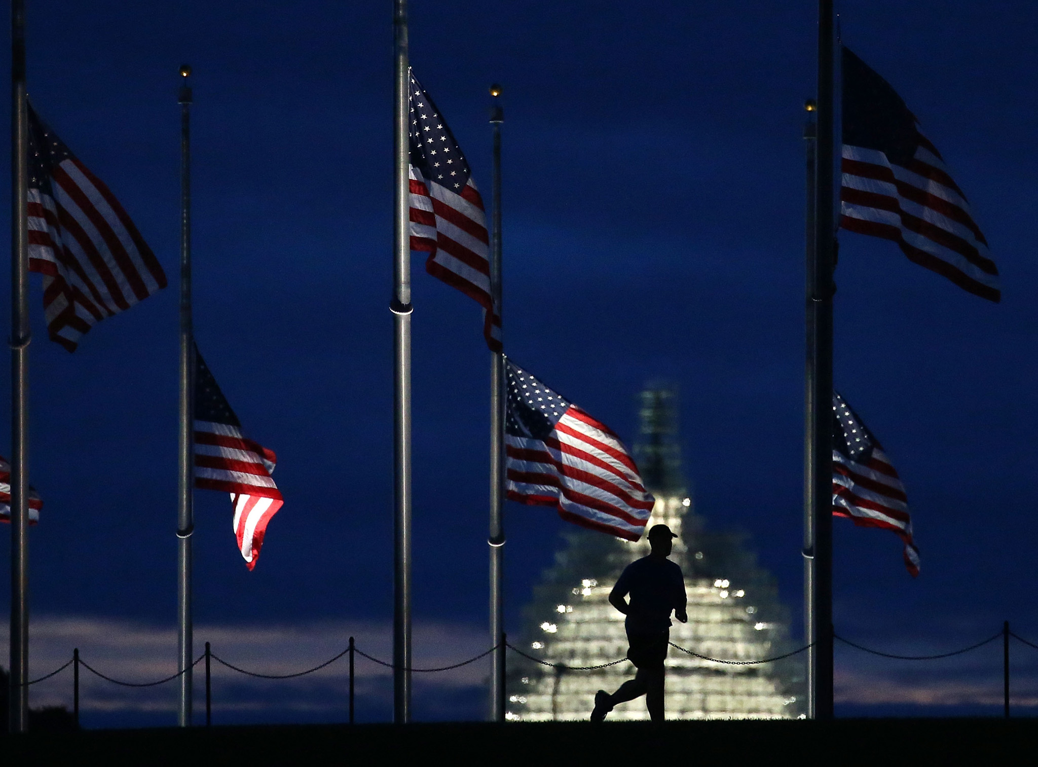 President Obama, First Lady Hold Moment Of Silence On Anniversary Of 9/11 Attacks...WASHINGTON, DC - SEPTEMBER 11:  A man jogs past a row of American flags that have been lowered to half staff on the Washington Monument grounds, near the US Capitol on September 11, 2015 in Washington, DC. Today marks the fourteenth anniversary of the September 11, 2001 attacks when terroristists high jacked airliners and flew them in the World Trade Center and the Pentagon.  (Photo by Mark Wilson/Getty Images)
