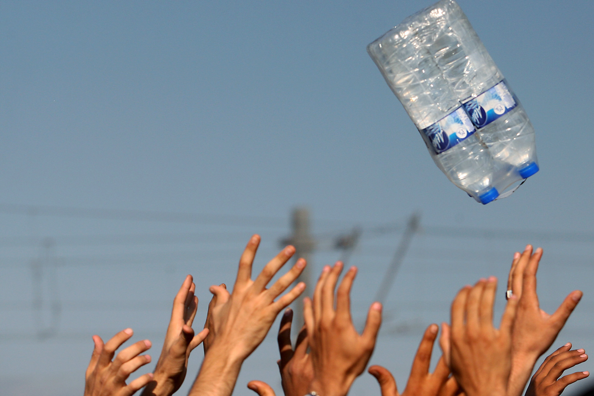 "Migrants raise hands to catch bottles of...Migrants raise hands to catch bottles of waters thrown by volunteers of humanitarian organizations as they wait to cross the Greek-Macedonian border near the vilage of Idomeni, northern Greece, on 4 September, 2015. Europe is facing an ""unprecedented humanitarian and political crisis"" as it struggles with the huge influx of refugees and migrants, the European Commission's vice-president Frans Timmermans said Thursday. ""We must find European responses to a problem that cannot be resolved by countries individually,"" Timmermans said ahead of talks with Greek Prime Minister Vassiliki Thanou on a crisis that has seen more than 230,000 people land on Greek shores this year. AFP PHOTO /Sakis MitrolidisSAKIS MITROLIDIS/AFP/Getty Images"