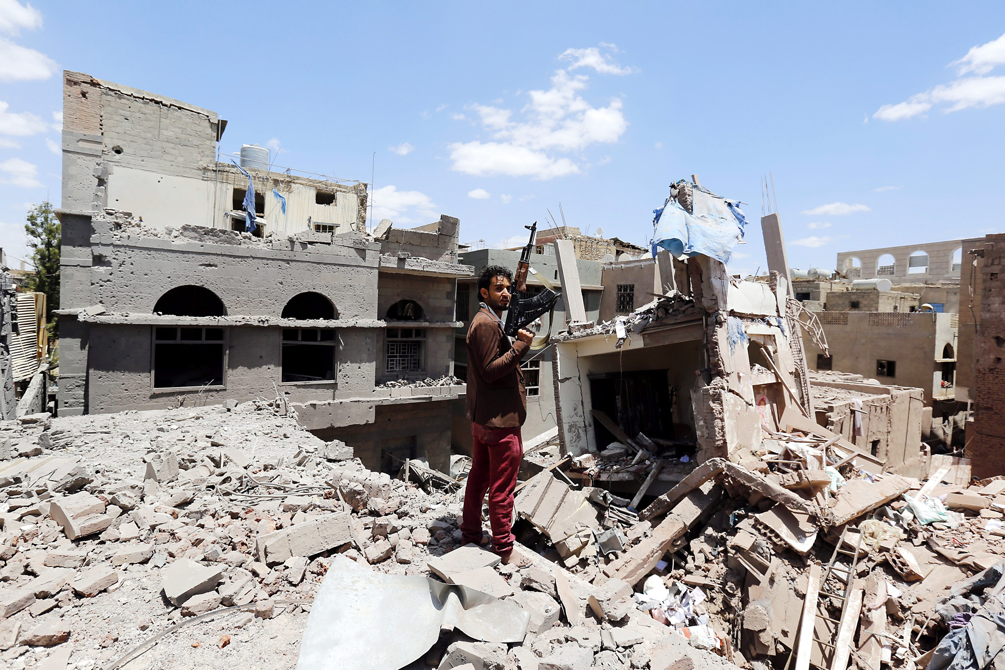 Saudi-led airstrikes intensify on Sanaía...epa04923741 An armed Yemeni man stands amid the rubble of destroyed houses after they were hit by an airstrike carried out by the Saudi-led coalition in Sanaía, Yemen, 10 September 2015. The Saudi-led coalition against Yemen's Houthi rebels hinted that an attack on Sana'a was not imminent despite the recent build-up of Gulf forces in Marib province, east of the rebel-held capital. Yemen has seen six months of intense conflict since the mainly Shiite Houthi rebels advanced on the southern city of Aden, forcing President Abd Rabu Mansour Hadi to flee to Riyadh.  EPA/YAHYA ARHAB