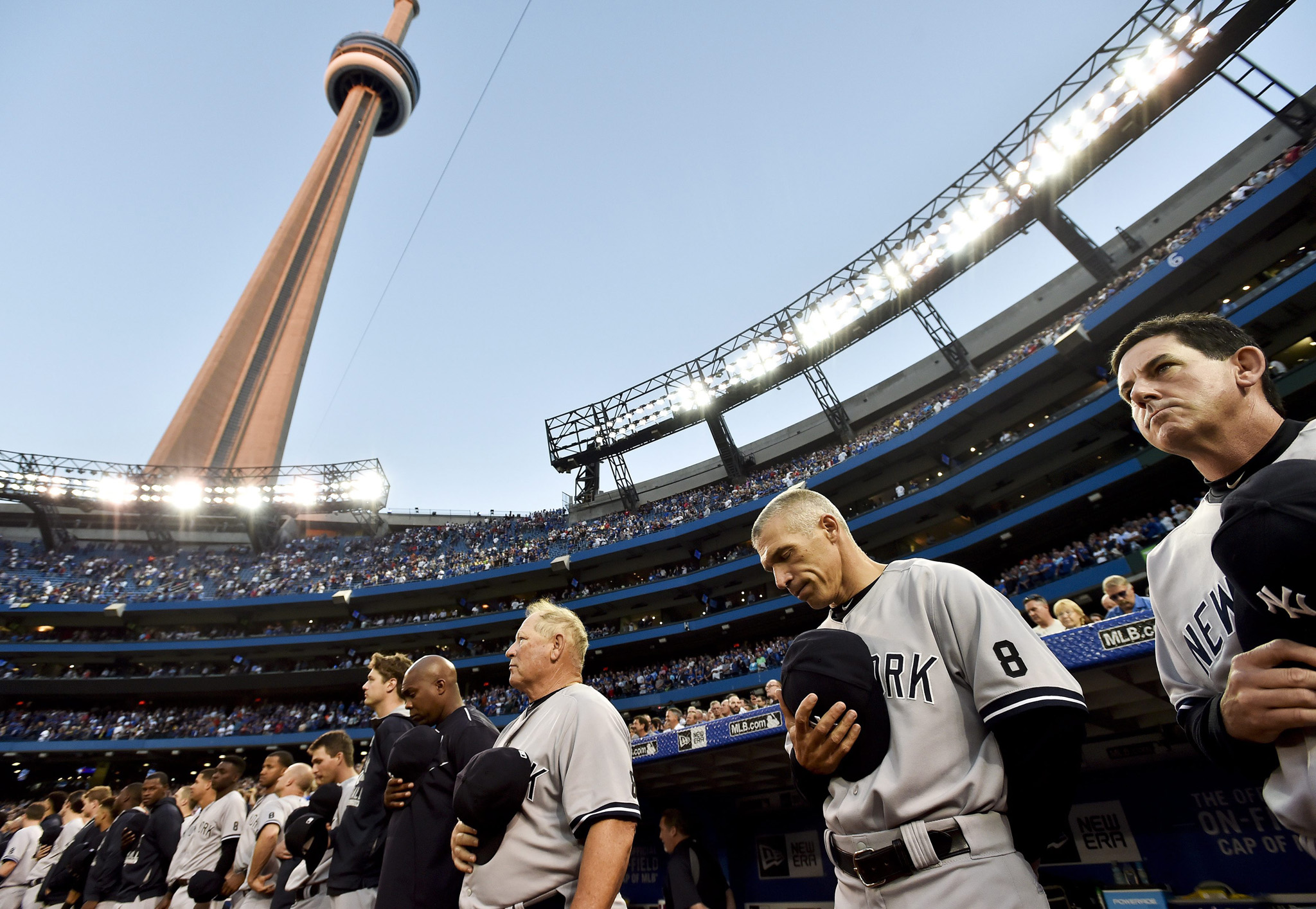New York Yankees manager Joe Girardi, second from right, and players and coaches take part in a moment of silence as they wear the No. 8 to remember Hall of Fame catcher Yogi Berra, who died Tuesday, before the Yankees' baseball game against the Toronto Blue Jays in Toronto on