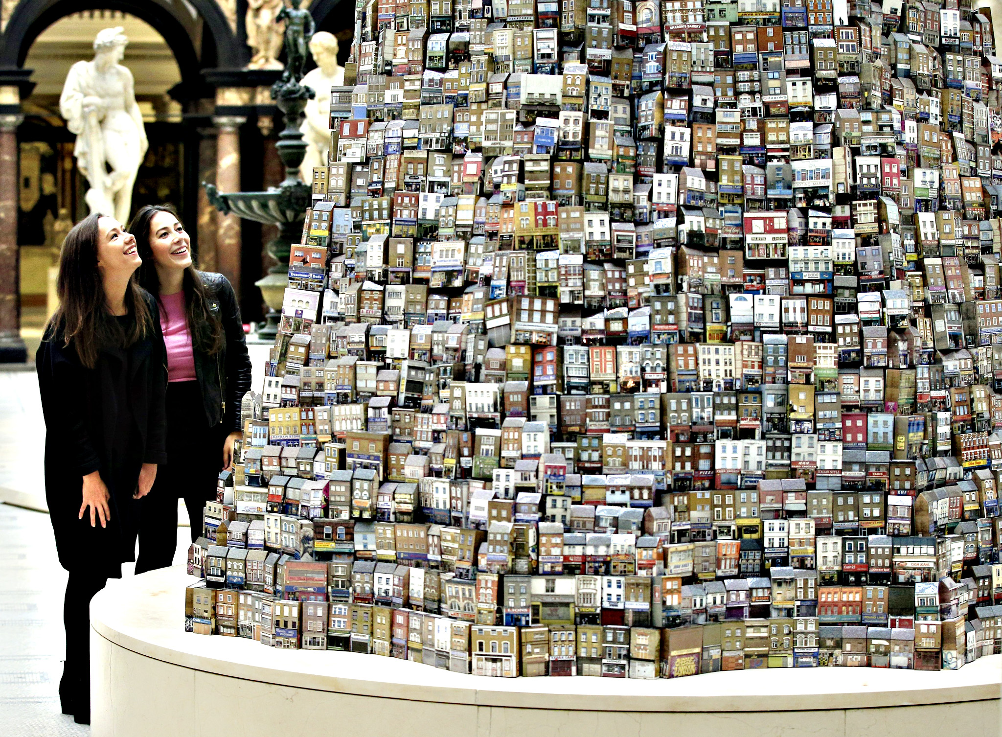 People view 'Tower of Babel' by artist Barnaby Barford, a six metre tall ceramic sculpture composed of 3,000 individual pieces depicting genuine London shop fronts displayed in the V&A Museum's Medieval land Renaissance Galleries