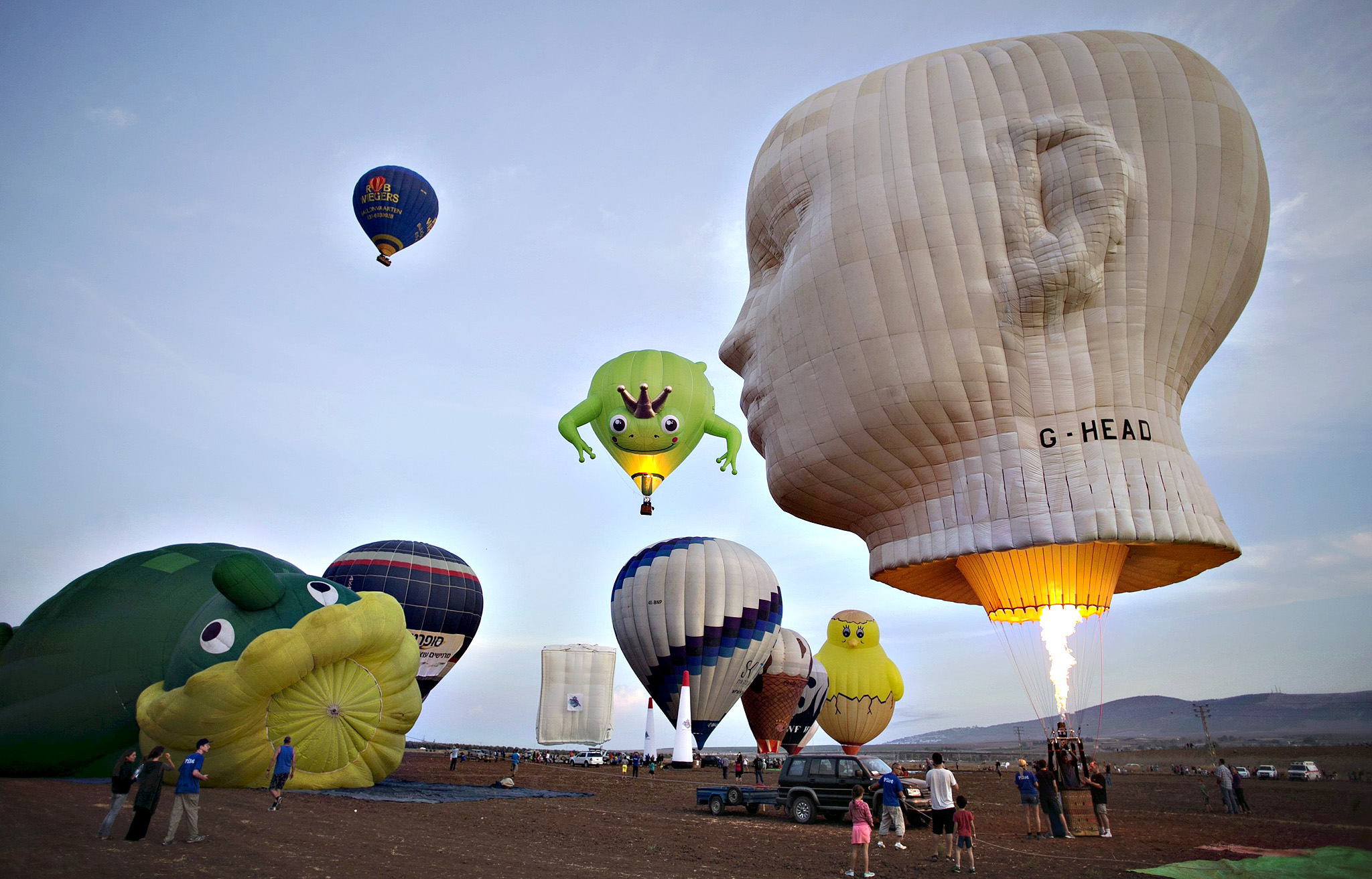 Hot air balloons are prepared for a flight as others take off during an international hot air balloon festival at Maayan Harod National park in northern Israel on Wednesday