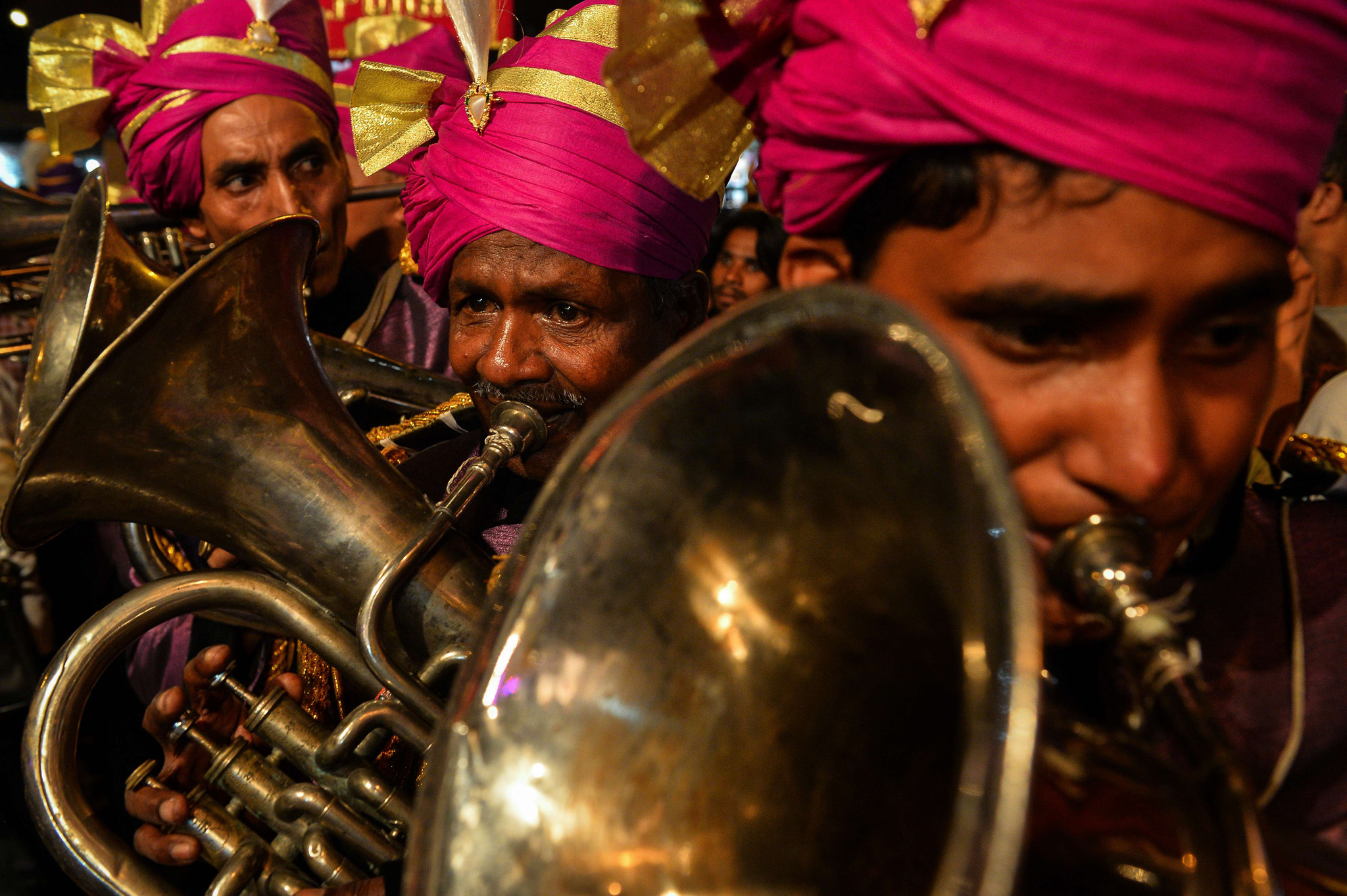 Members of an Indian wedding band play brass instruments during a religious procession for the Hindu festival Ganesh Chaturthi in New Delhi