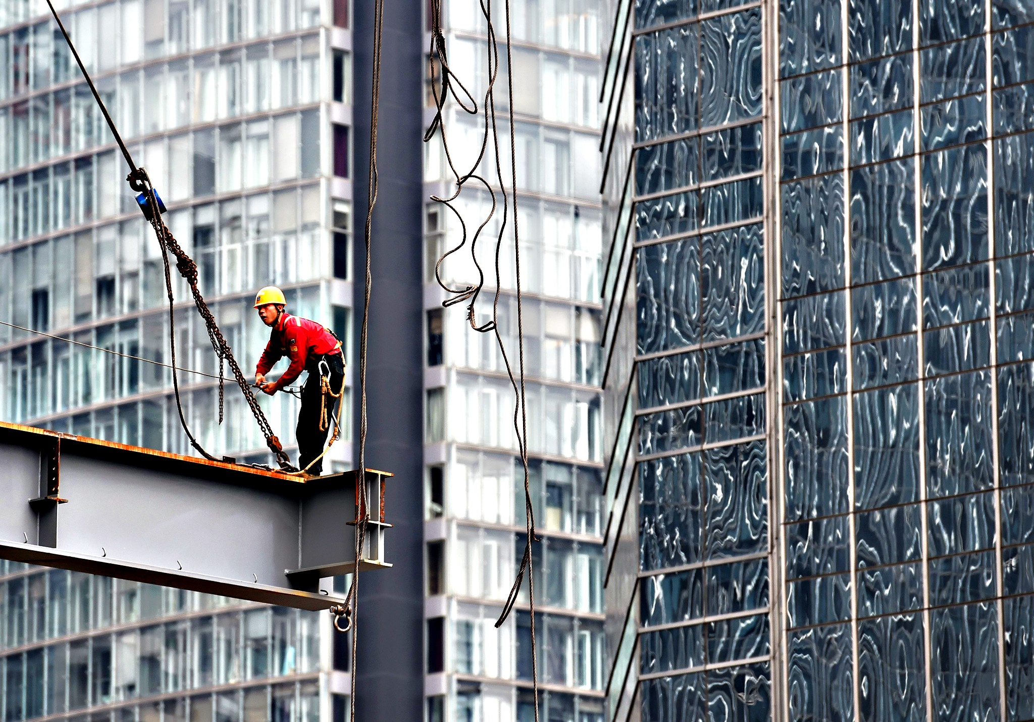 A worker stands on a beam on a construction site in Beijing on Wednesday. China's government says the world's second largest economy is expanding at its slowest for 25 years -- and according to analysts the real figures could be much lower -- and the slowdown has world markets rattled.