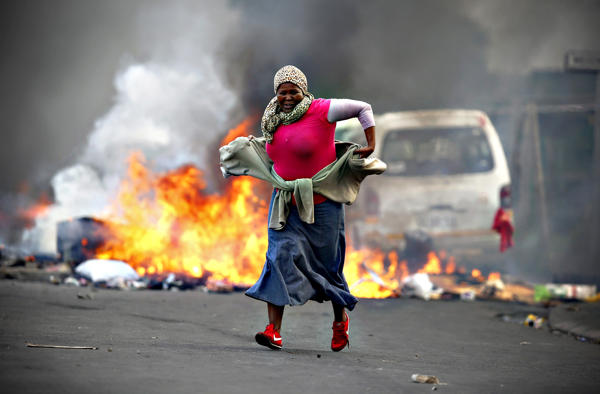 A South African resident of Masiphumelele runs past a burning barricade during a protest against the lack of policing in Masiphumelele, Cape Town, South Africa,  29 September 2015. According to local reports the protest was sparked by the court appearance 29 September of some residents arrested in connection with vigilante killings. The area has been volatile for weeks with community members angered at the lack of policing in the impoverished area. Two weeks ago suspected criminals were killed by a mob accused of being behind the death and rape of 15 year old Amani Pula