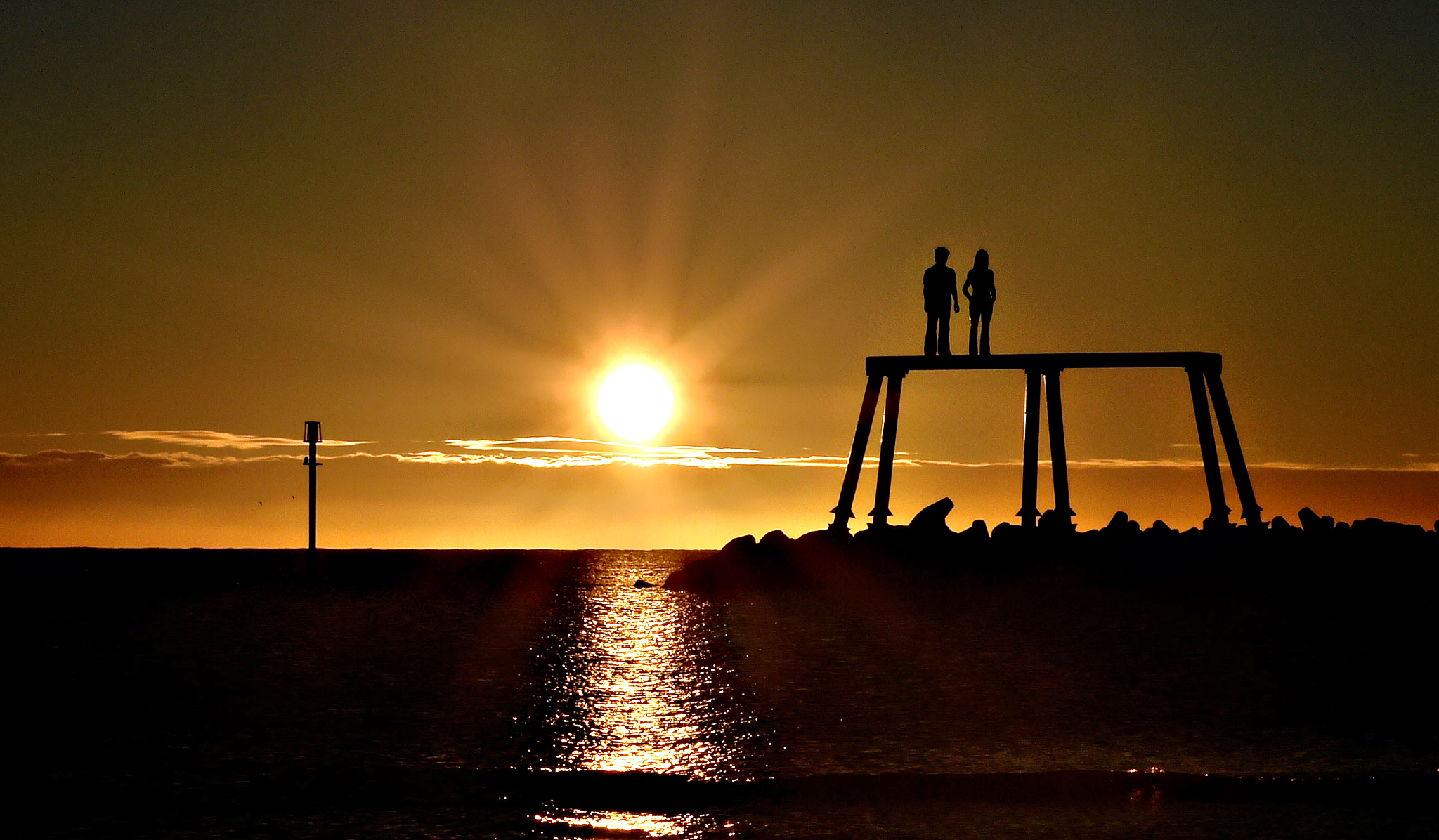 The autumn sun rises over the north sea next to The Couple by artist Sean Henry at Newbiggin-by-the-Sea, Northumberland, as mixed conditions and colder nights are in store for Britain following the arrival of the autumn equinox