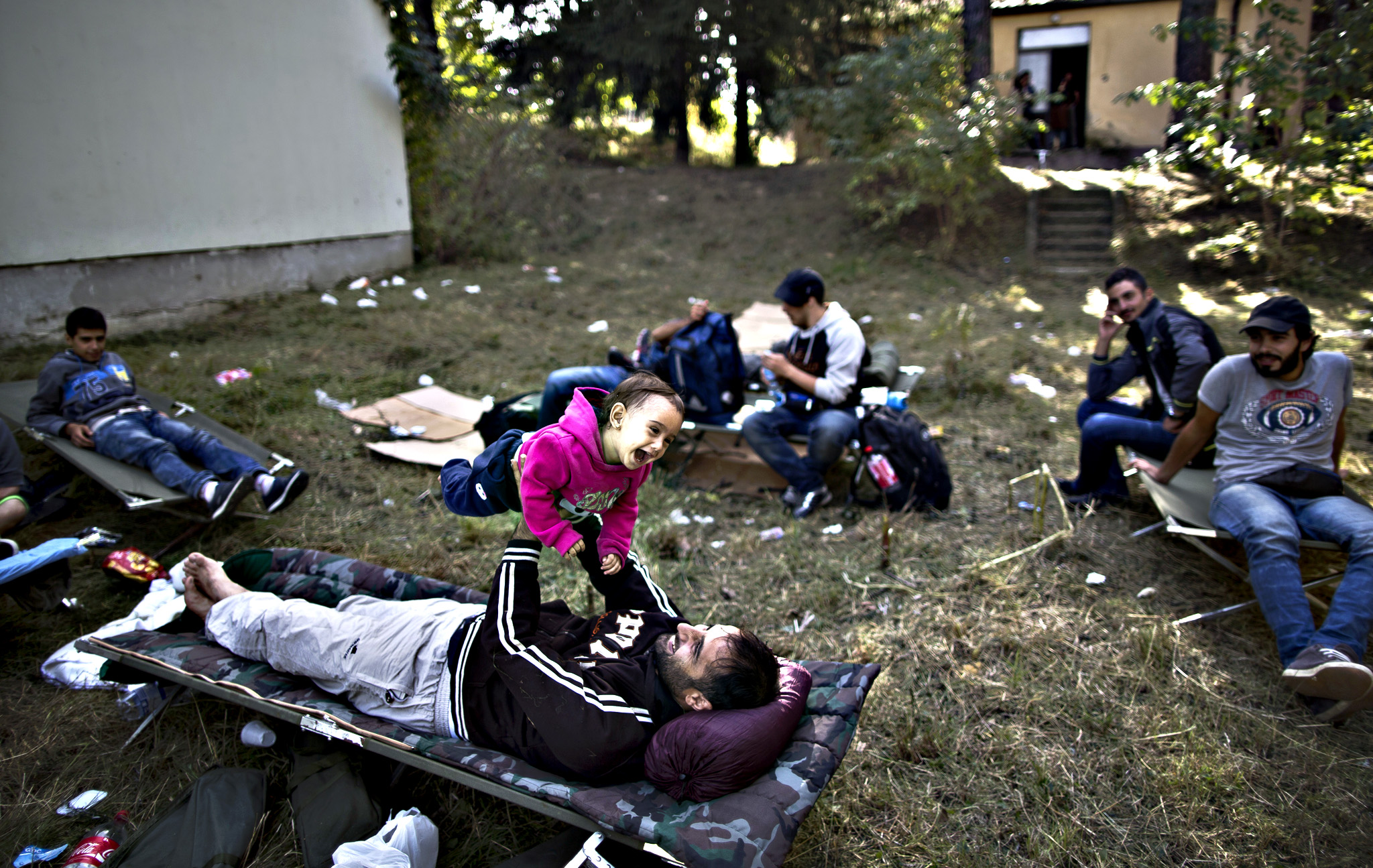 A Syrian refugee man plays with his daughter after spending night near an abandoned military barrack in Beli Manastir, near Hungarian border, northeast Croatia, Friday, Sept. 18, 2015. Croatian police say some 13,300 migrants have entered the country from Serbia since the first groups started arriving more than two days ago