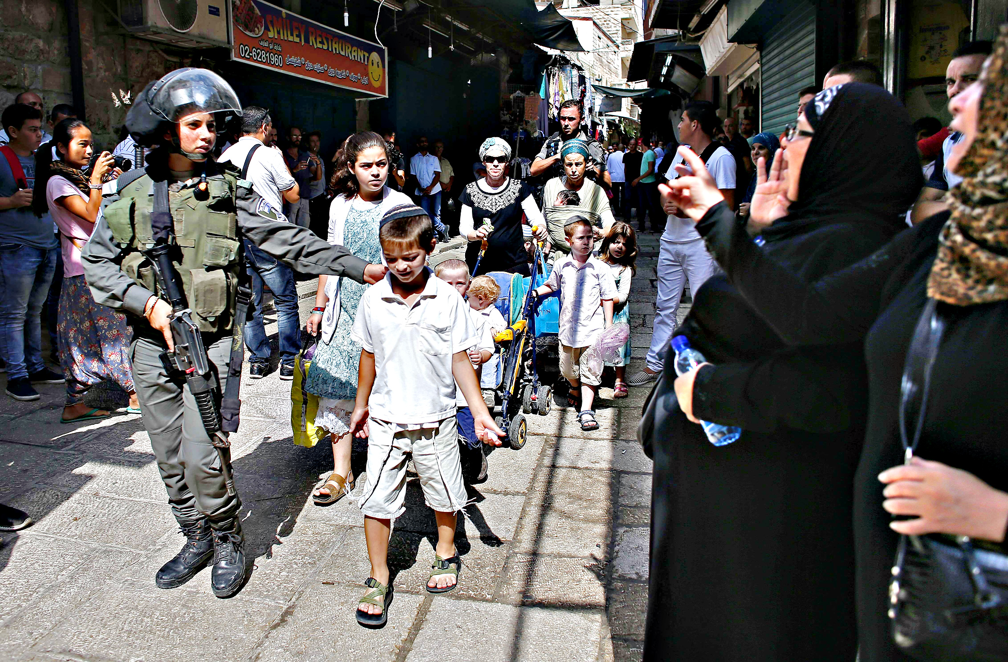 "Palestinain women (R) shout ""Allahu Akbar"" (God is the greatest) as Israeli security forces escort Jewish worshippers coming from the Western Wall, Judaism holiest site, vrossing through the Muslim quarter in Jerusalem's Old City on September 15, 2015 during scuffles between Palestinian Muslims and Israeli security forces. Muslims and Israeli police clashed at Jerusalem's flashpoint Al-Aqsa mosque compound for a third straight day as Jews celebrated their new year and protesters vowed to protect Islam's third-holiest site"