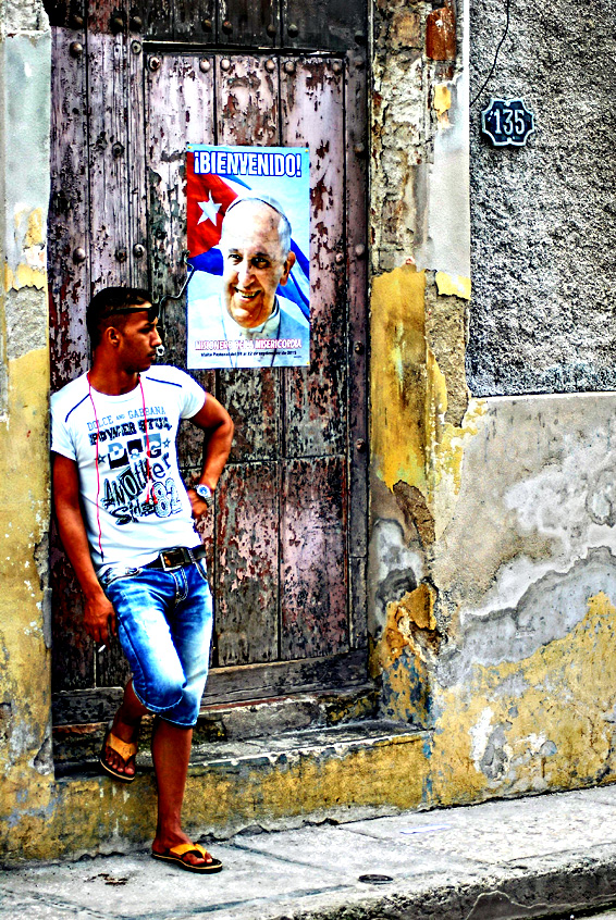 A portrait of welcoming Pope Francis hangs from a door in Holguin, on Friday. The pope is visiting Cuba from Saturday, the first stop on a trip that also will take him to the United States. In Cuba, he will visit Havana, the northeastern city of Holguin and Santiago de Cuba on the southeastern end of the island.