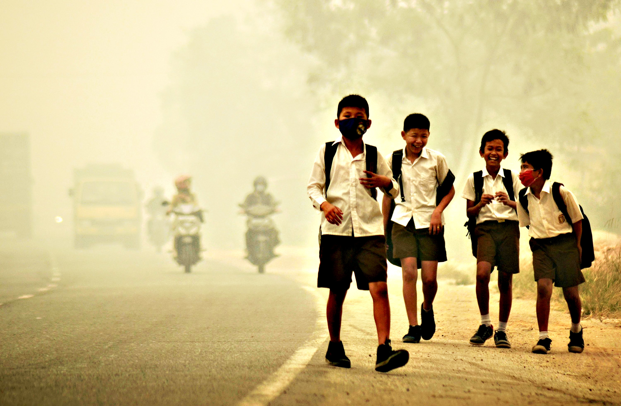 "Students walk along a street as they are released from school to return home earlier due to the haze in Jambi, Indonesia's Jambi province, September 29, 2015 in this picture taken by Antara Foto. Indonesia has sent nearly 21,000 personnel to fight forest fires raging in its northern islands, the disaster management agency said on Tuesday, but smoke cloaks much of the region with pollution readings in the ""very unhealthy"" region in neighboring Singapore"